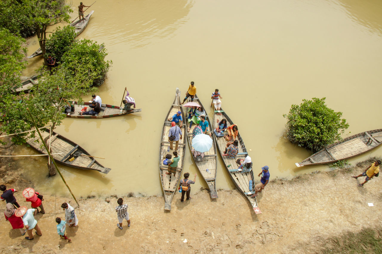 real people, high angle view, men, large group of people, transportation, boat, water, mode of transport, nautical vessel, river, day, outdoors, tree, nature, occupation, lifestyles, women, fisherman, riverbank, sky, people