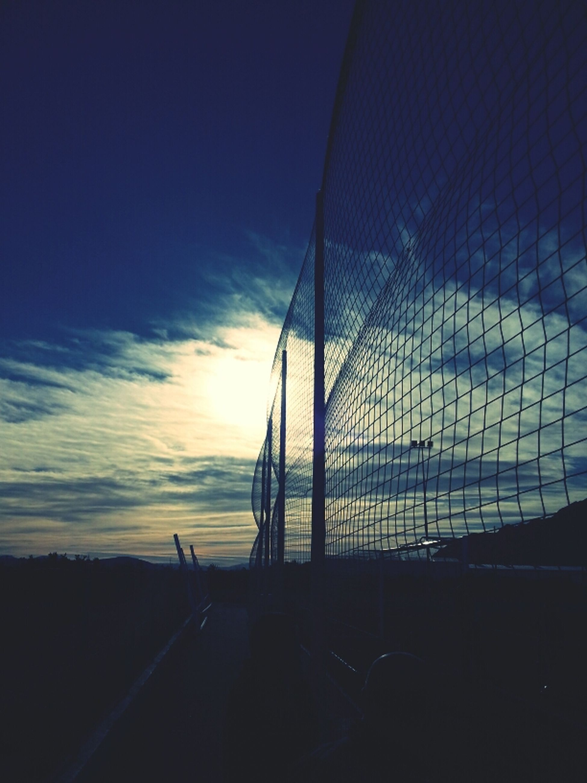 sky, sunset, silhouette, transportation, road, railing, cloud - sky, connection, blue, dusk, cloud, built structure, bridge - man made structure, outdoors, sunlight, no people, nature, the way forward, fence, tranquility