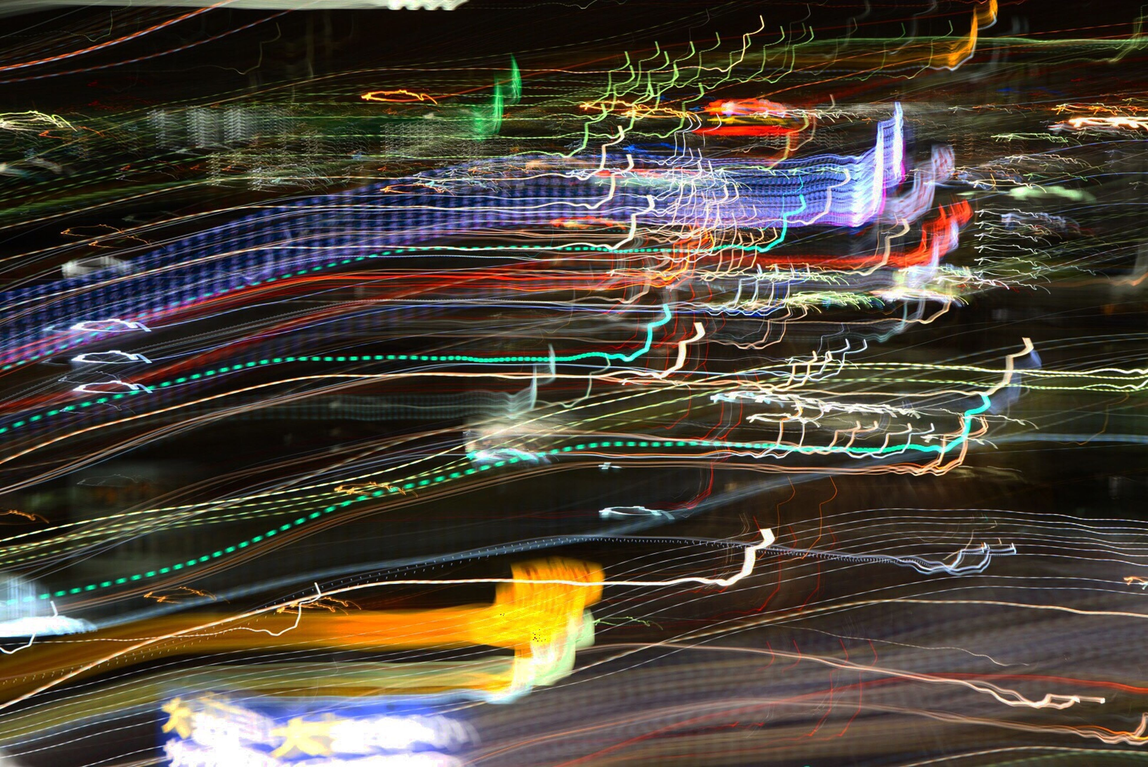 illuminated, light trail, night, motion, long exposure, speed, low angle view, multi colored, outdoors, engineering, development, modern, no people, city life, national landmark