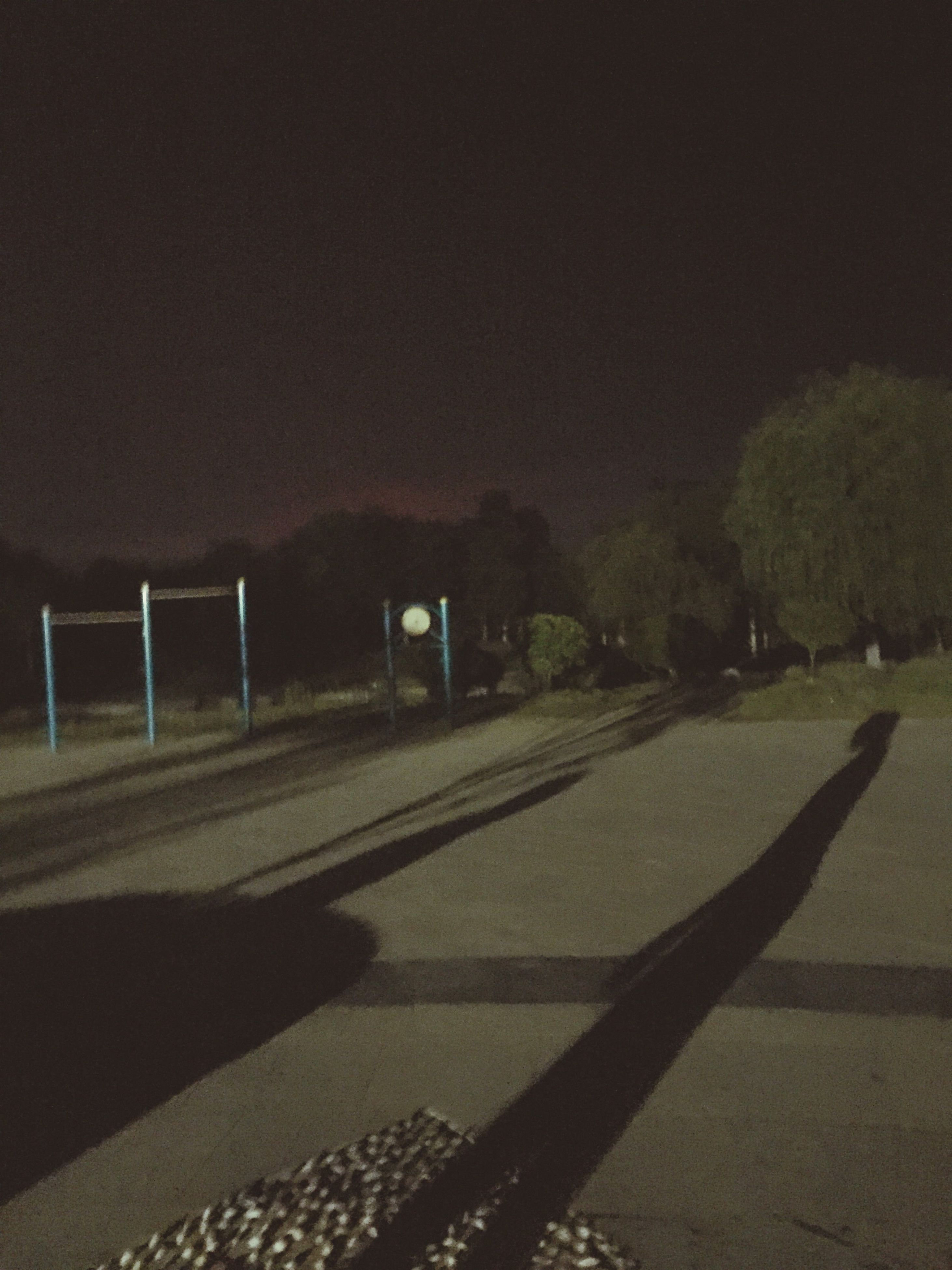 night, illuminated, tree, road, street light, street, dark, railing, transportation, outdoors, copy space, tranquility, no people, nature, clear sky, empty, tranquil scene, sky, high angle view, growth