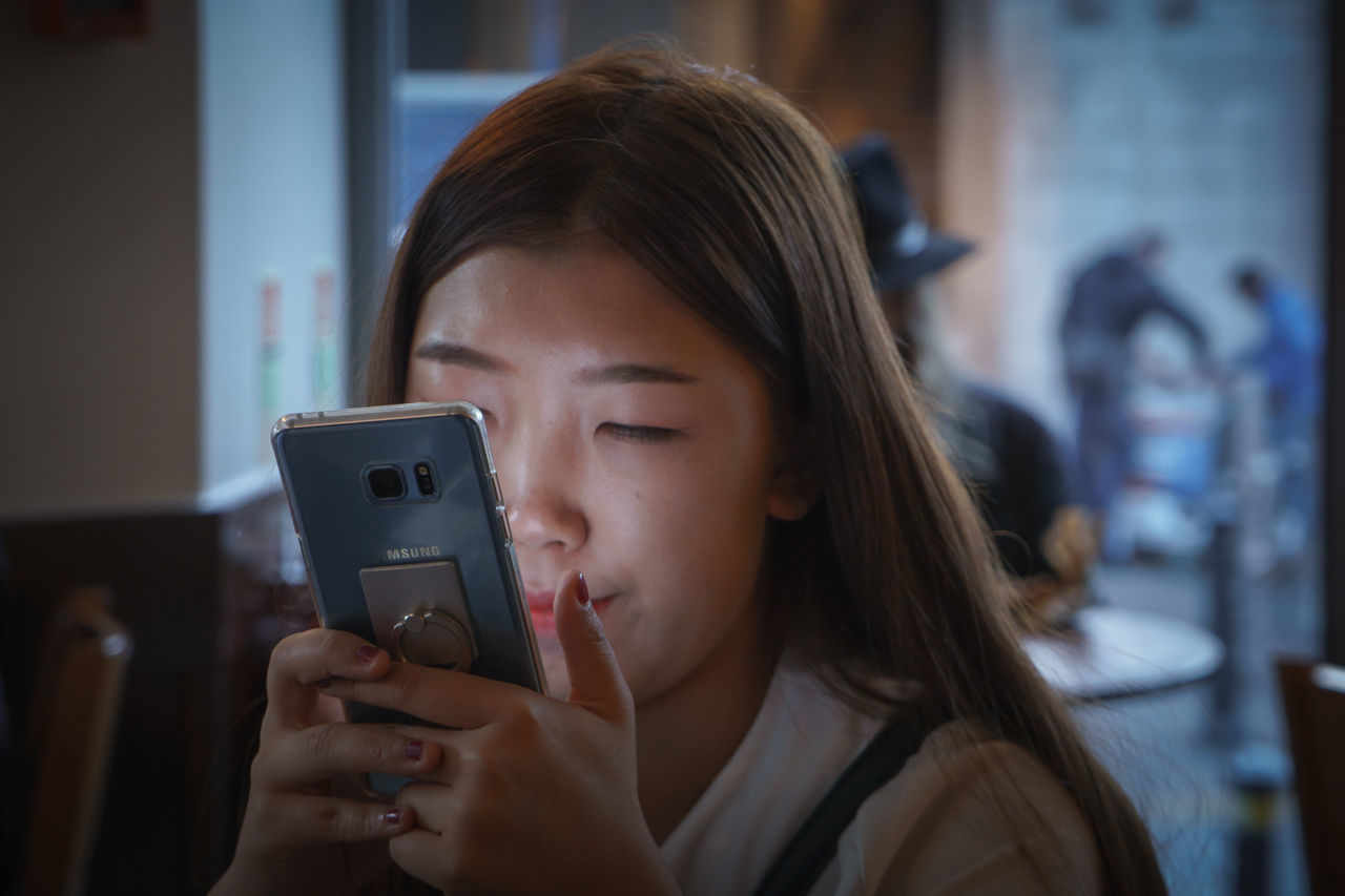 One of Asian girl looking at hers Samsung mobile phone in a coffee shop Asian  Communication Connection Dramatic Angles Headshot Lifestyles Light Source Looking At Phone Mobile Mobile Phone Photographing Photography Themes Samsung Smart Phone TakeoverContrast Technology Text Messaging The Culture Of The Holidays TheCreatorClass Using Phone Wireless Technology Young Adult Young Women London Lifestyle Enjoy The New Normal London City Life