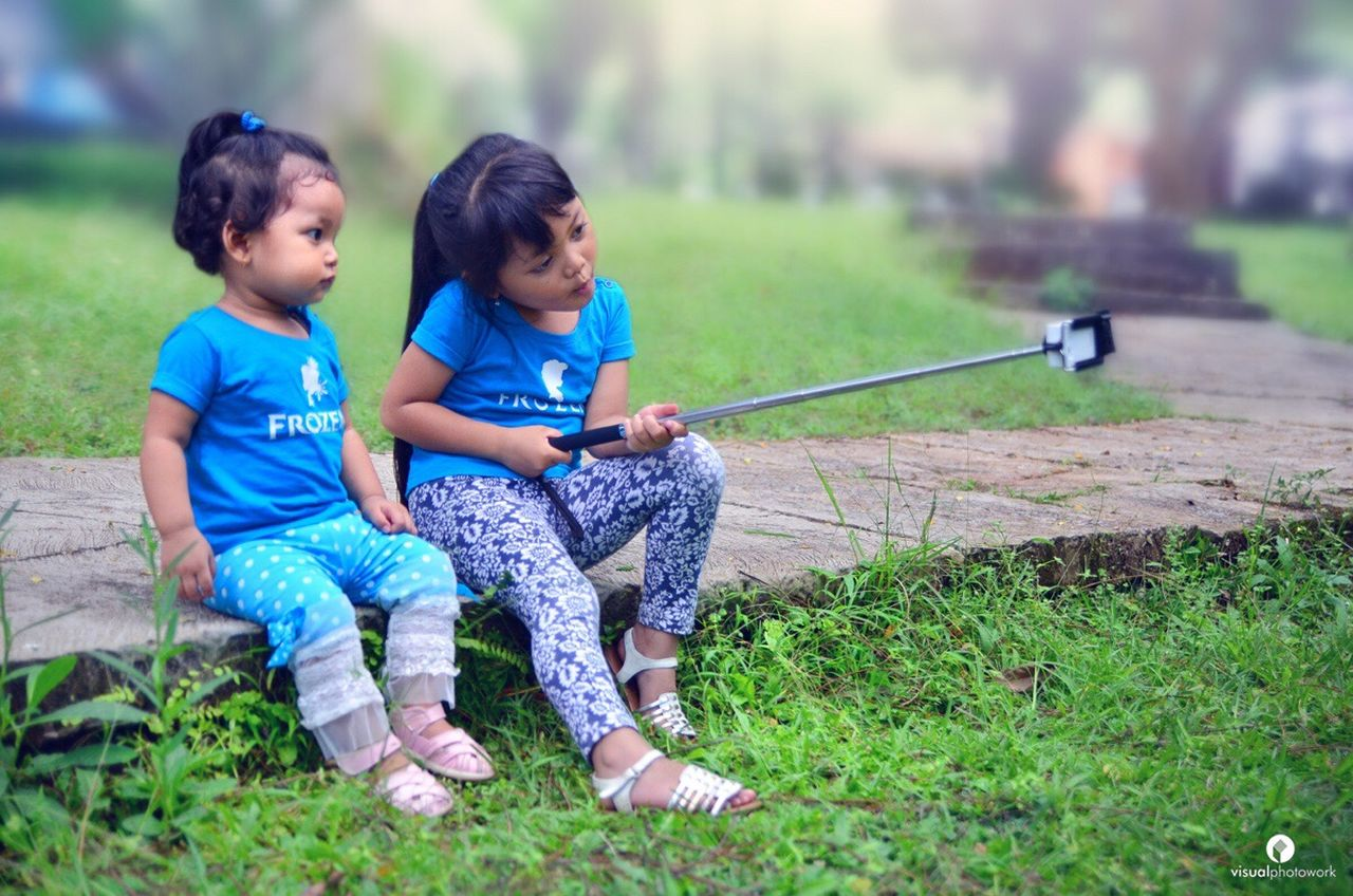 wefie Child Childhood Two People Sitting Playing Casual Clothing Cute Outdoors Green Color Grass Happiness Togetherness Girls Children Only First Eyeem Photo