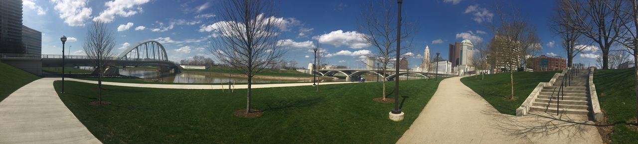 architecture, built structure, sky, day, grass, outdoors, building exterior, cloud - sky, no people, tree, panoramic, city, sport, nature, skateboard park, soccer field