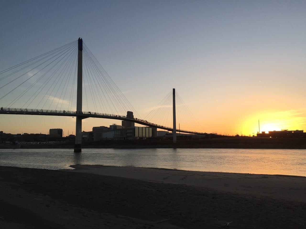 Footbridge Over River During Sunset