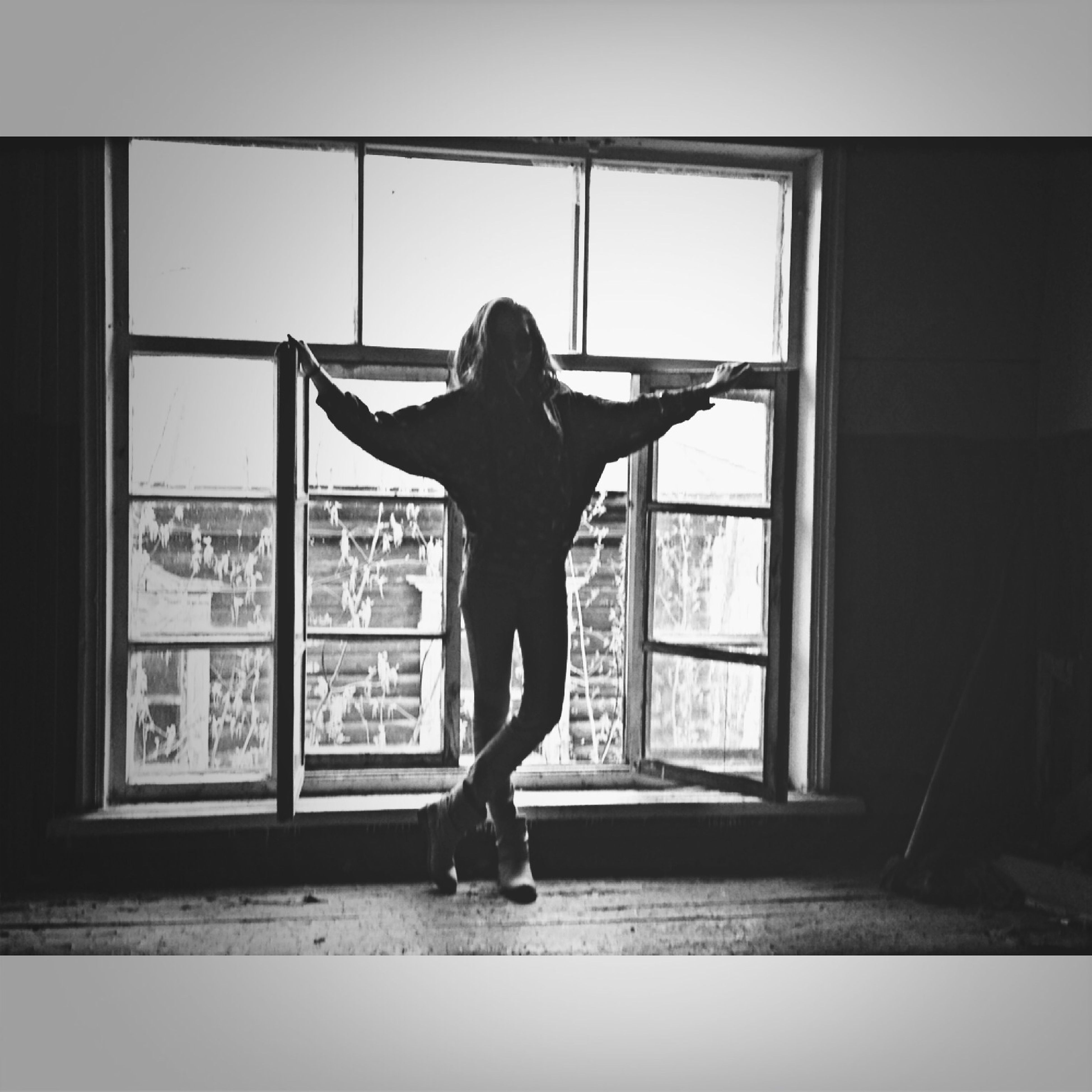 full length, indoors, young adult, lifestyles, standing, young women, casual clothing, rear view, window, architecture, leisure activity, built structure, person, front view, looking through window, side view, day, long hair