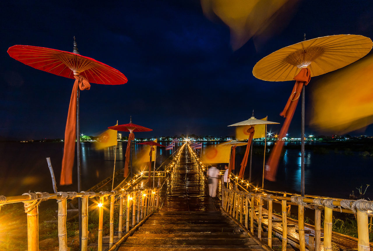 PHAYAO, THAILAND - JULY 19, 2016: The bamboo bridge, The bamboo bridge of Wat Ti Lok Aram temple in kwan phayao off freshwater lake of Thailand. Day is the important Buddhist. ASIA Bamboo Bridge Buddhist Built Structure City Cloud - Sky Culture Illuminated Important Kwan Phayao Lighting Equipment Multi Colored Nature Night No People Orange Color Outdoors Sky Temple Thailand The Way Forward Tourism Travel Destinations Wat Ti Lok Aram