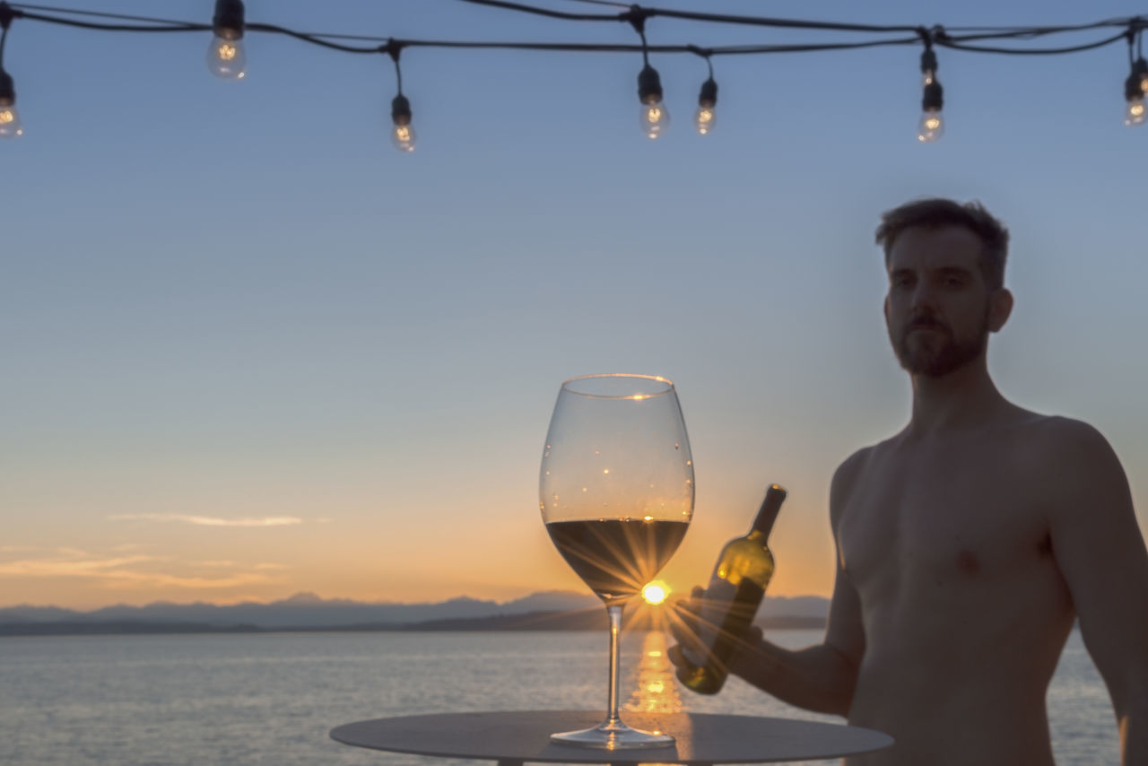 Wineglass On Table With Man Holding Bottle While Standing At Beach Against Sky During Sunset