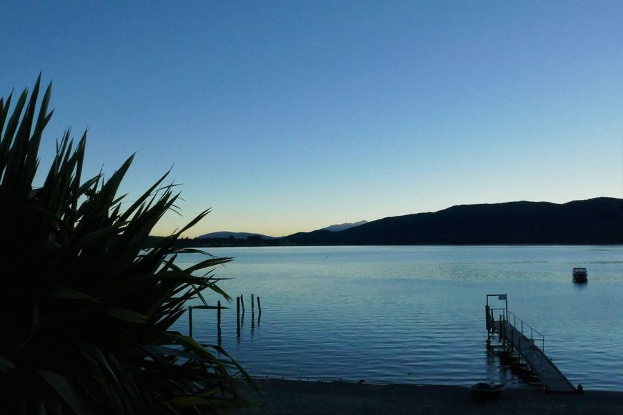 Sunset behind the mountains at te anau Beauty In Nature Blue Boat Clear Sky Jetty Mountain Nature New Zealand New Zealand Landscape New Zealand Scenery No People Outdoors Pier Plants Scenics Seagulls Sunset Tranquil Scene Tranquility Twilight Twilight Sky Water Water Reflections Waterfront