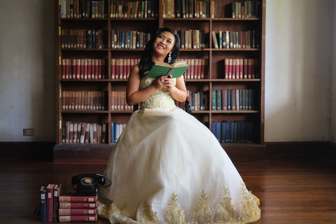 Birthday Book Bookshelf Bride Debut  Debutant Education Full Length Girl Indoors  Learning Library Library Looking At Camera One Person Portrait Real People Shelf Sitting Smiling Student Study Vintage Young Adult Young Women