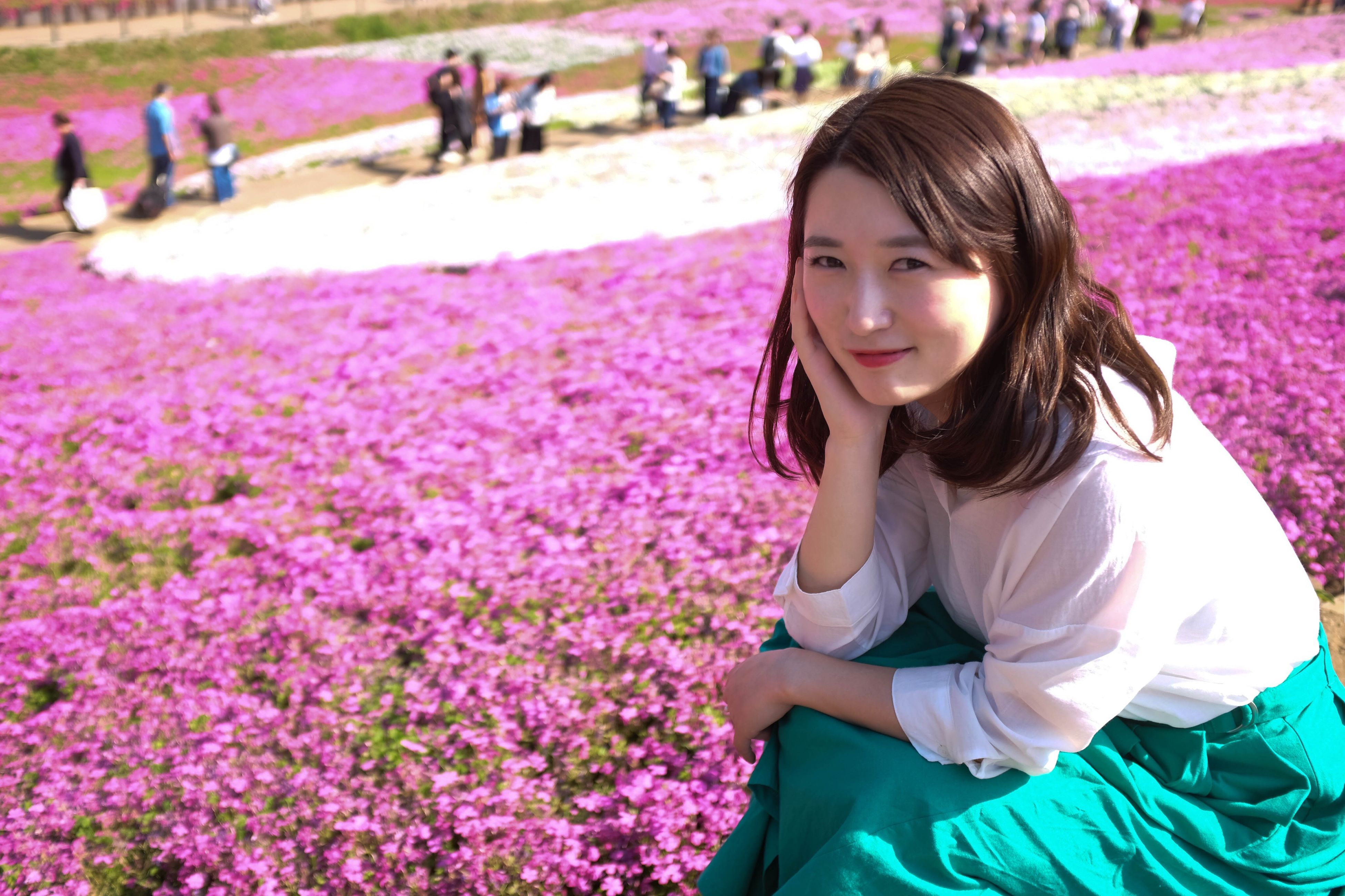 real people, one person, young adult, beautiful woman, purple, casual clothing, looking at camera, flower, young women, day, outdoors, pink color, focus on foreground, leisure activity, portrait, lifestyles, smiling, nature, people