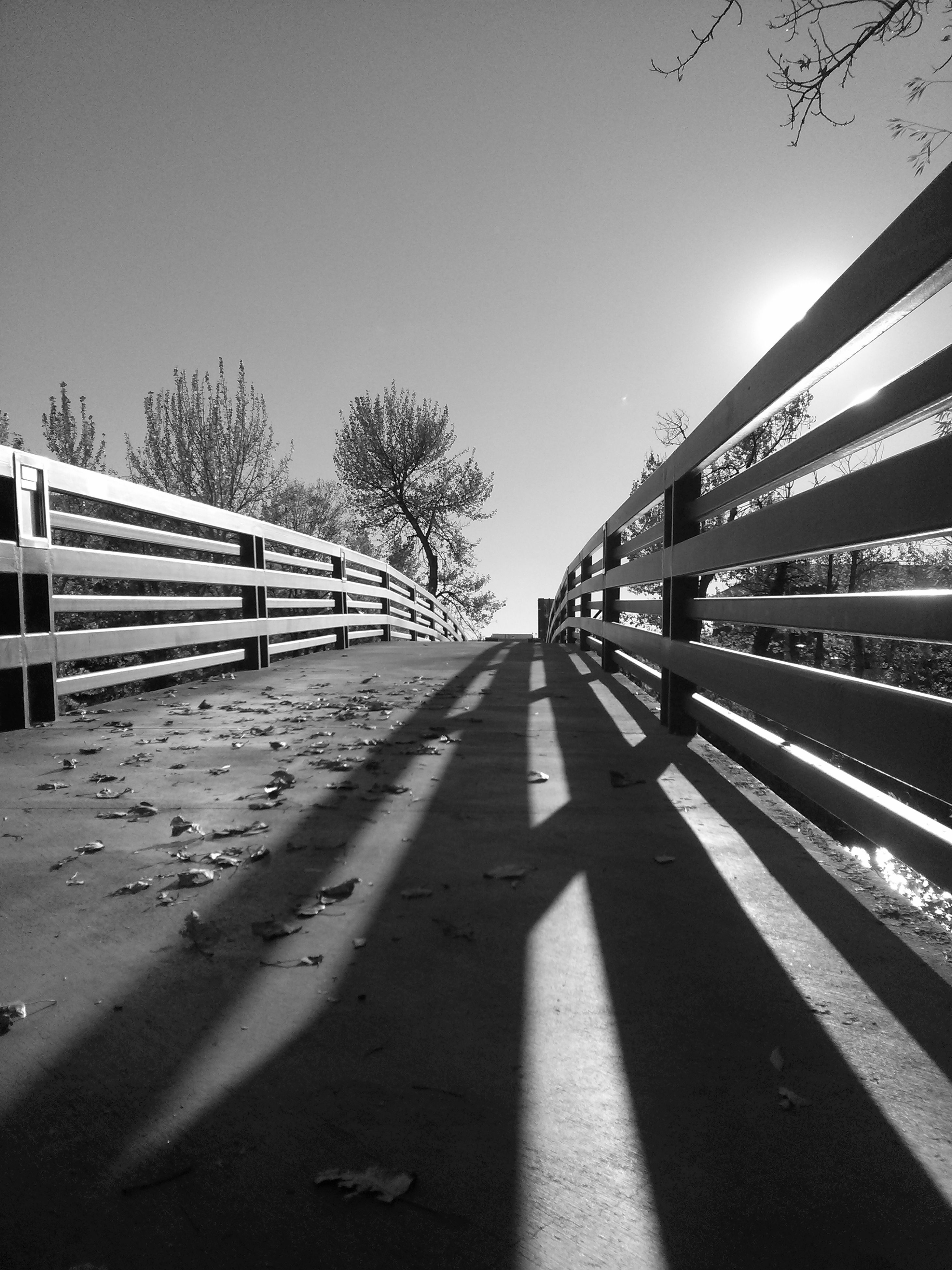 the way forward, clear sky, transportation, diminishing perspective, road marking, vanishing point, road, long, railing, copy space, built structure, connection, empty, sky, architecture, sunlight, shadow, outdoors, railroad track, bridge - man made structure