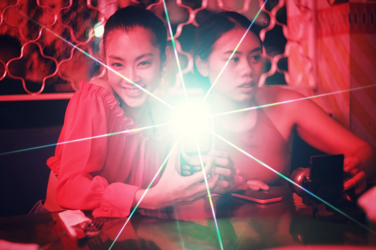 lens flare, real people, illuminated, sparkler, enjoyment, togetherness, smiling, indoors, young women, lifestyles, holding, fun, leisure activity, night, happiness, looking at camera, boys, young adult, childhood, men, portrait, close-up, human hand, people