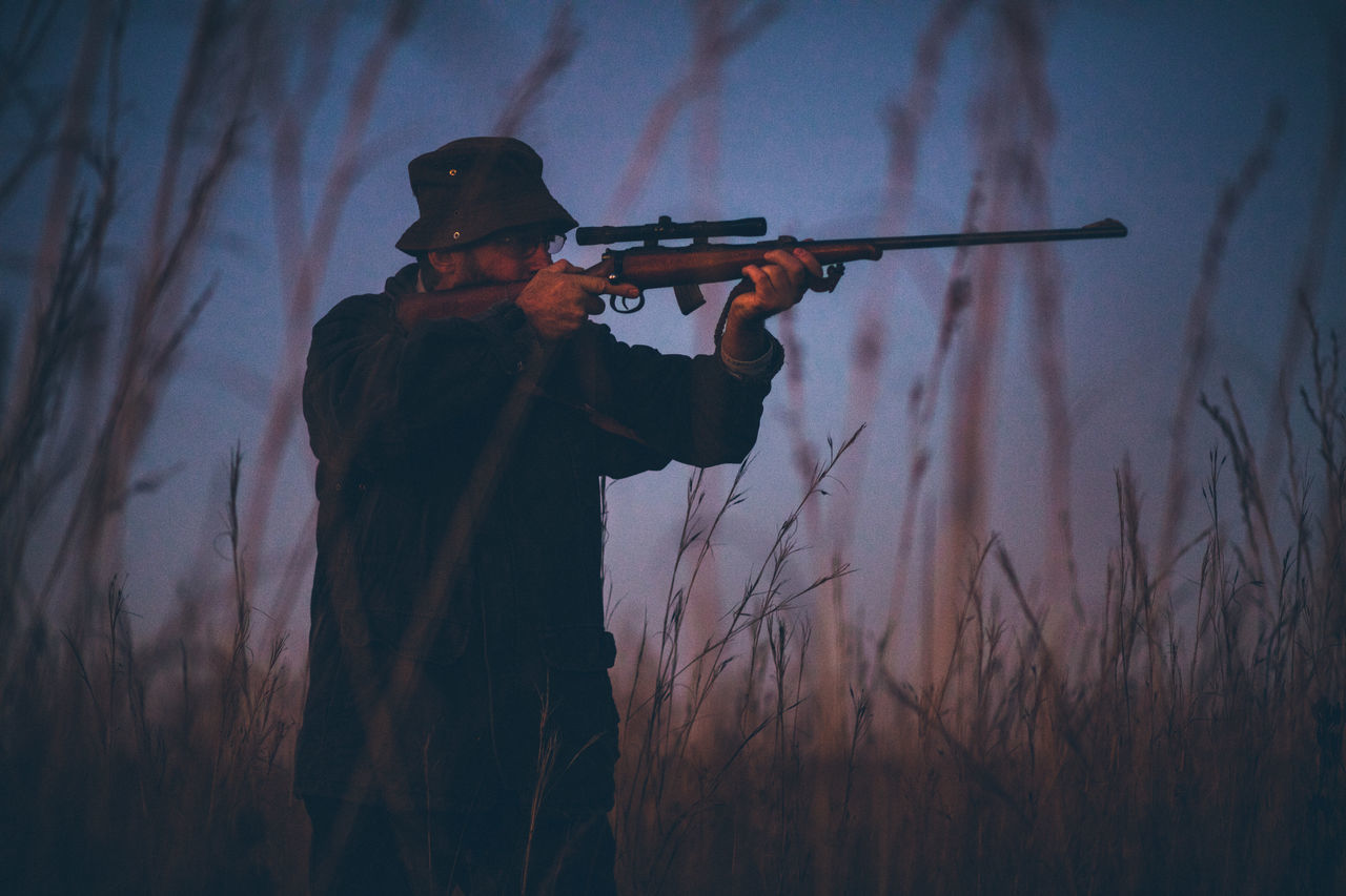 Hunter aiming prey on field with his rifle in sunrise Agriculture Aiming Field Hobby Hunter Hunting Lifestyle Long Grass Man Morning Nature Observe People Permit Shooting Shotgun Silhouette Skill  Sniper Sunrise Weapon Western Wild Animals Wilderness Wildlife