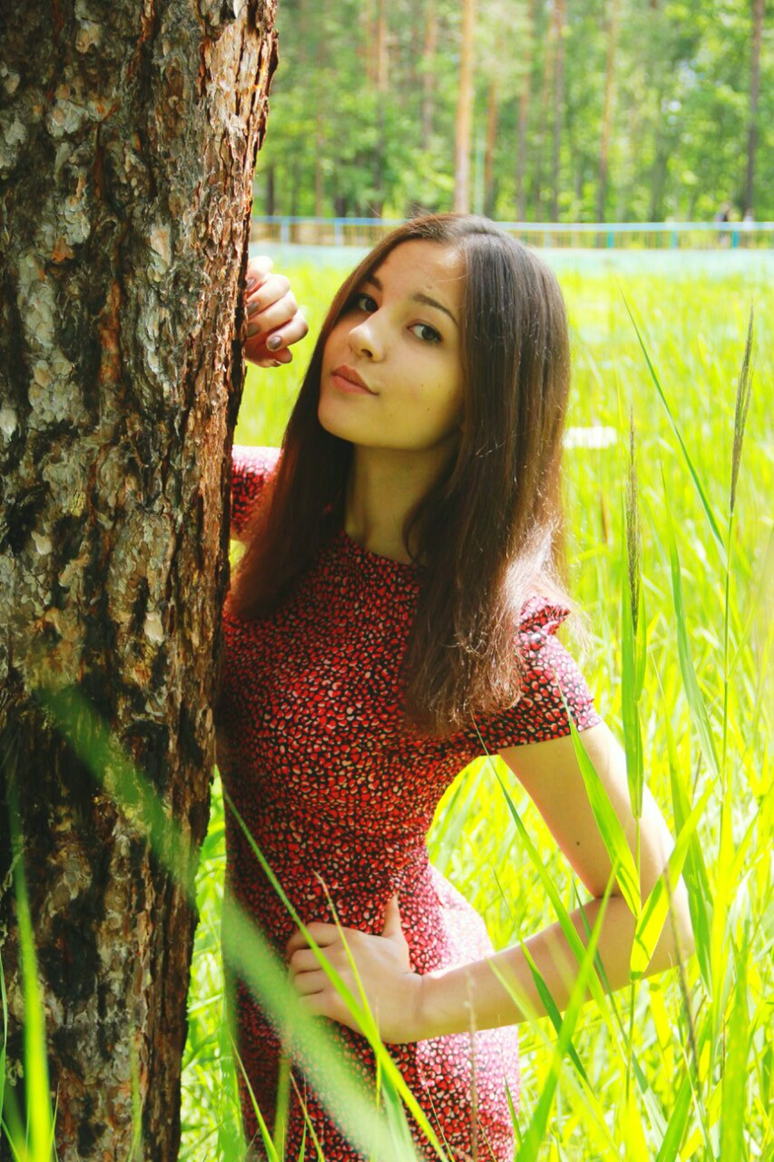 person, long hair, young women, young adult, lifestyles, tree, leisure activity, casual clothing, portrait, waist up, looking at camera, front view, standing, tree trunk, focus on foreground, forest, smiling