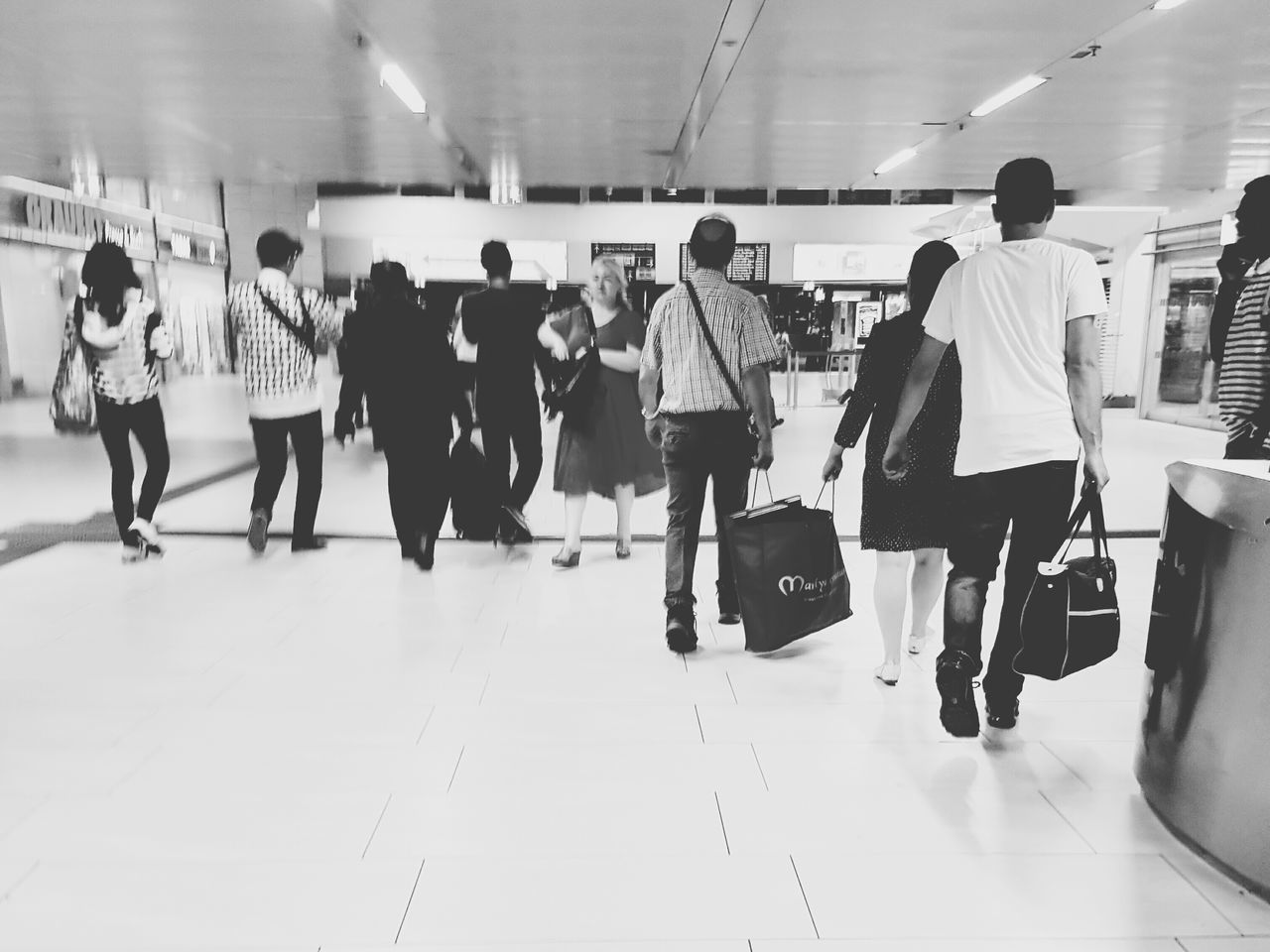 real people, indoors, men, women, walking, full length, large group of people, lifestyles, leisure activity, motion, luggage, illuminated, crowd, day, adult, people