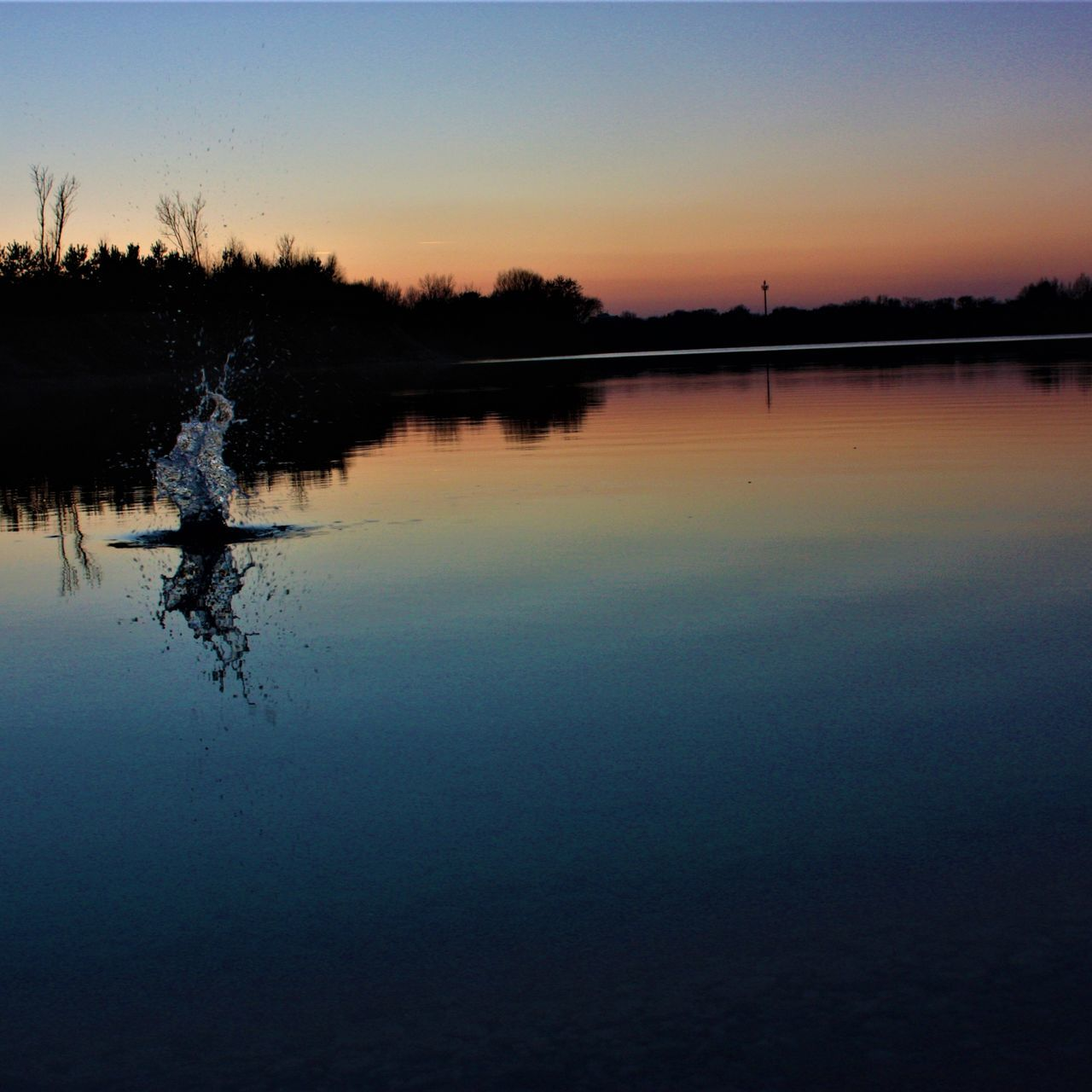 sunset, reflection, water, silhouette, nature, beauty in nature, tranquil scene, tree, lake, scenics, outdoors, tranquility, waterfront, sky, no people, clear sky, day