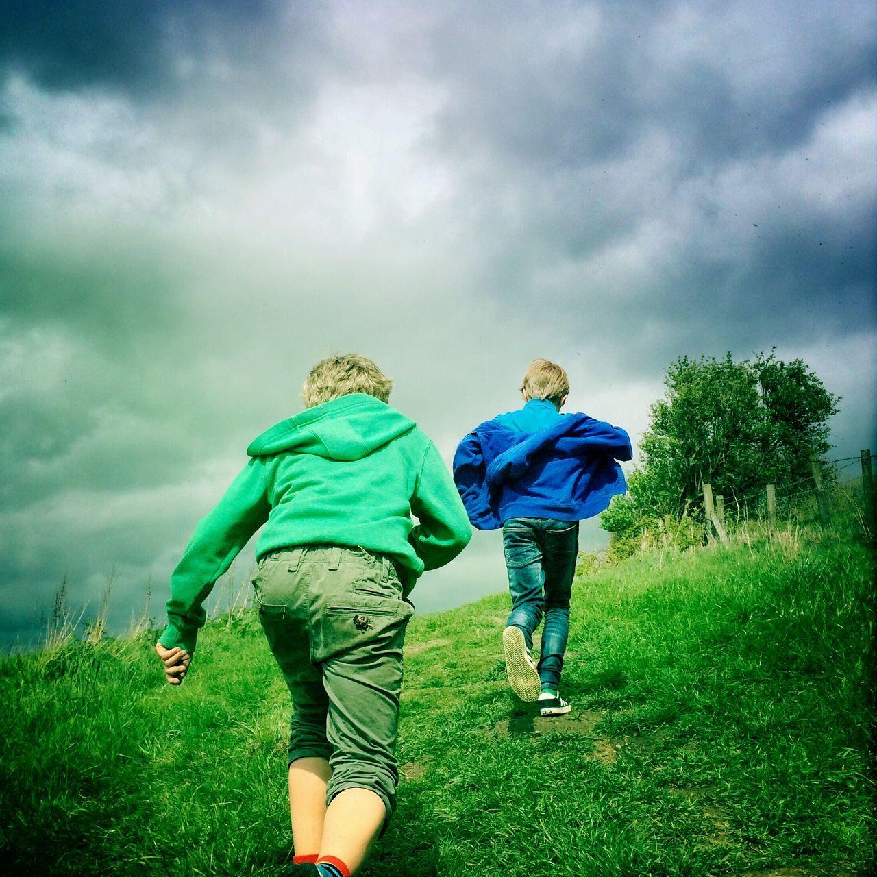 Rear View Of Boys Walking On Hill