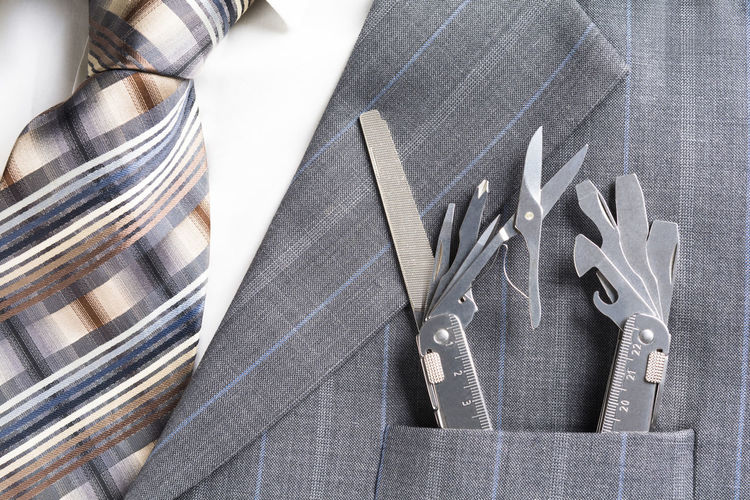 Multitool in pocket of businessman in a support/service concept Employee Leader Man SUPPORT Service Suit Assistance Backgrounds Boss Business Businessman Concept Corporate Costume Grey Manager Multi Multitool Pocket  Professional Solution Success Tie Tool Variation