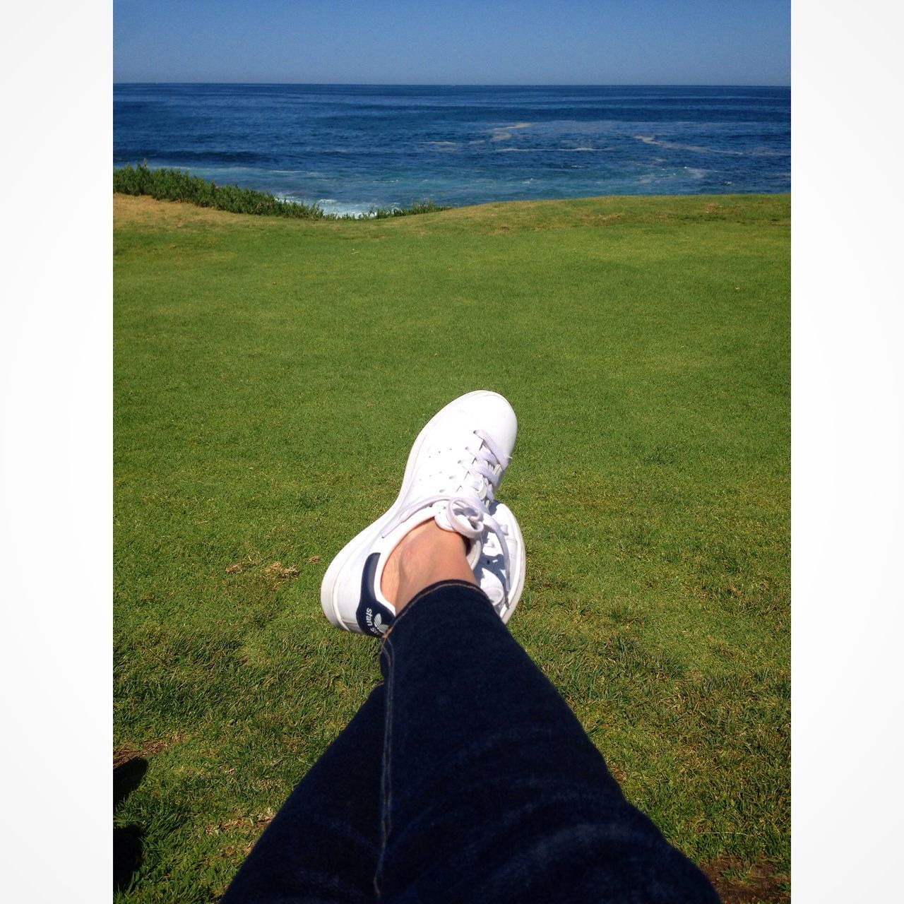 grass, low section, human leg, shoe, personal perspective, one person, day, real people, human body part, leisure activity, sea, standing, outdoors, green color, nature, horizon over water, water, sitting, men, golf, beauty in nature, close-up, sky, golf course, people