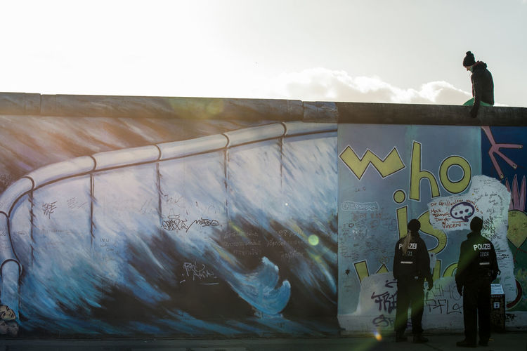 Graffiti Street Art Spraying Outdoors Day Water People Adult Sky Only Men Discover Berlin Berlinwall Who Is Who Policeman Policewoman Streetphotography Street Photography East Side Gallery, Berlin