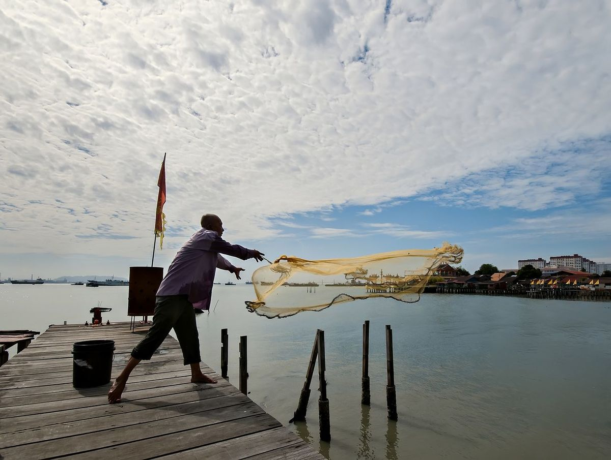 A fisherman people catching fish at jetty on beach Fisherman Fishermanslife Fishing Net Fishing Time Fishing Village Jetty Landscape Life Is A Beach Nature Net One Man Only One Person Only Men Outdoors People Working Standing