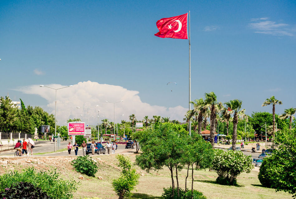 ANTALYA, TURKEY- MAY 12: Tourists in popular resort on May 12 2013. Antalya is a biggest international sea resort, located on the Turkish Riviera. Antalya Turkey City Editorial  Emblem  Famous Place Flag Of Turkey Landscape Large Group Of People Middle East National Flag Nature Outdoors Palm Trees Patriotism People Street Summer Sunny Day Symbol Tourism Tourist Resort Travel Destinations Turkey Turkish Riviera Waving Flag