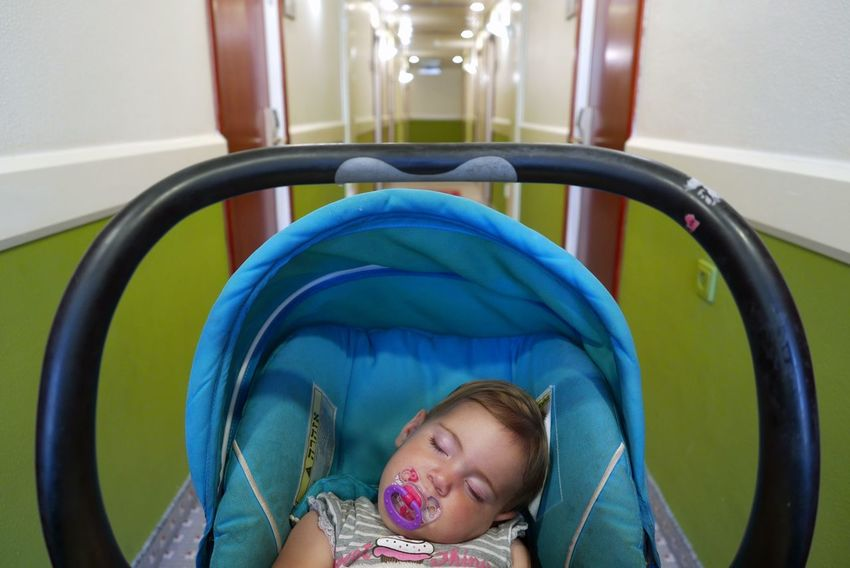 Baby sleeping with a pacifier in her stroller waiting in an hotel corridor Baby Sleeping Stroller Waiting Corridor Hotel