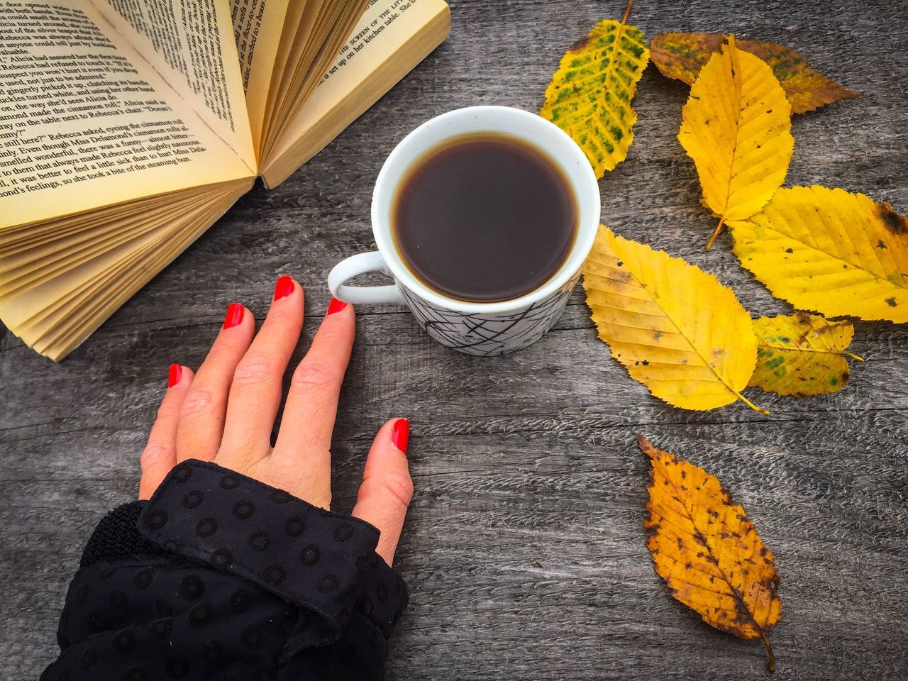 Cup of coffee on wooden table with yellow leaves and a book beside with a woman's hand with red nails Human Hand One Person Food And Drink Human Body Part Real People Table Freshness Close-up Day Hand Woman Nails Red Nails Cup Coffee Drink Coffeine Book Reading Autumn Fall Leaves Rustic Table Yellow