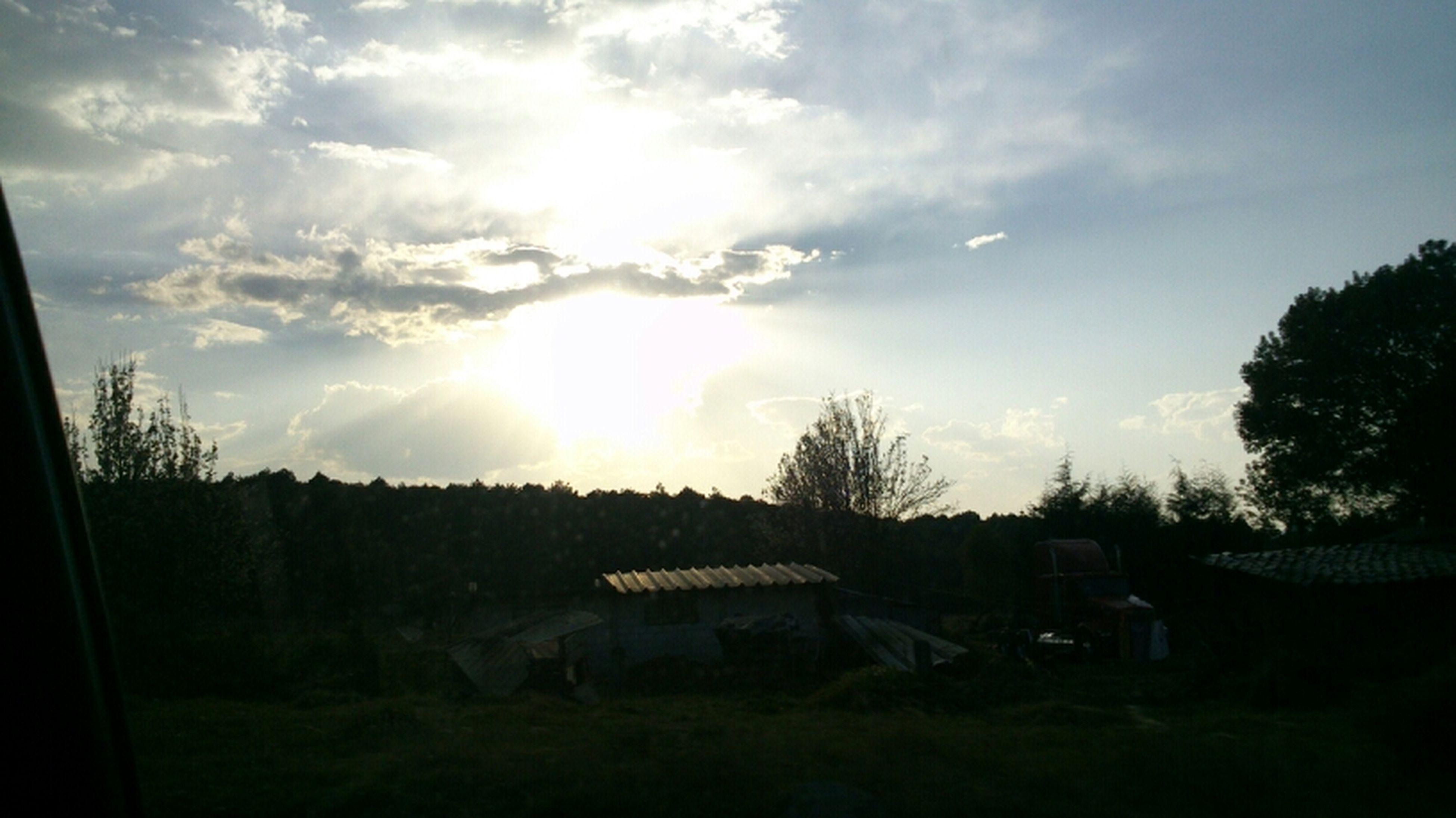 sky, tree, sun, silhouette, building exterior, built structure, house, cloud - sky, sunset, landscape, sunbeam, sunlight, architecture, field, nature, rural scene, tranquil scene, cloud, tranquility, scenics