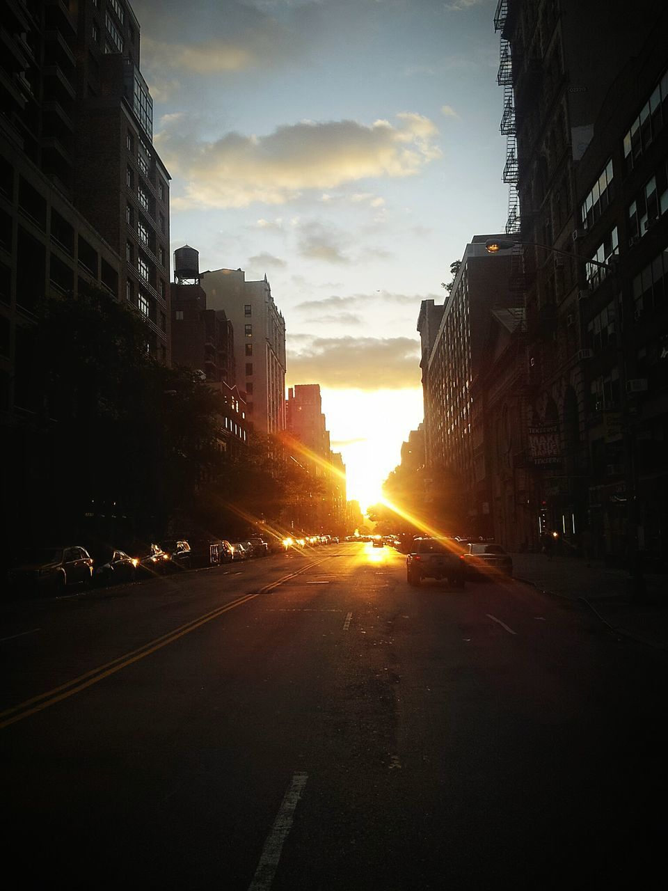 sunset, architecture, building exterior, city, built structure, sky, road, street, car, sun, transportation, sunlight, outdoors, the way forward, skyscraper, no people, cityscape, day