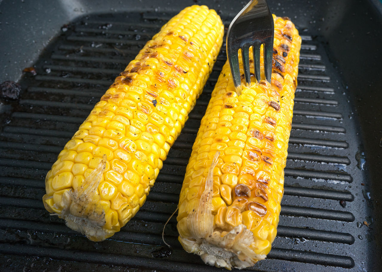 Close-Up Of Sweetcorns Cooking On Barbecue Grill