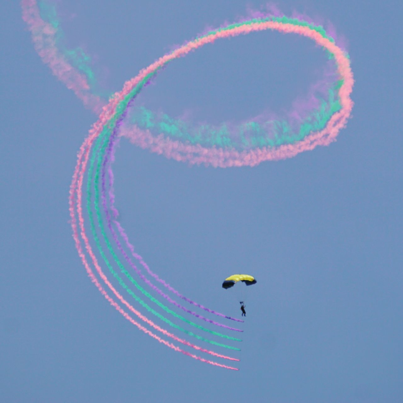 flying, low angle view, mid-air, parachute, vapor trail, airshow, multi colored, sky, transportation, extreme sports, adventure, air vehicle, outdoors, clear sky, leisure activity, aerobatics, blue, real people, day, skydiving, nature, stunt, paragliding, one person, beauty in nature, fighter plane