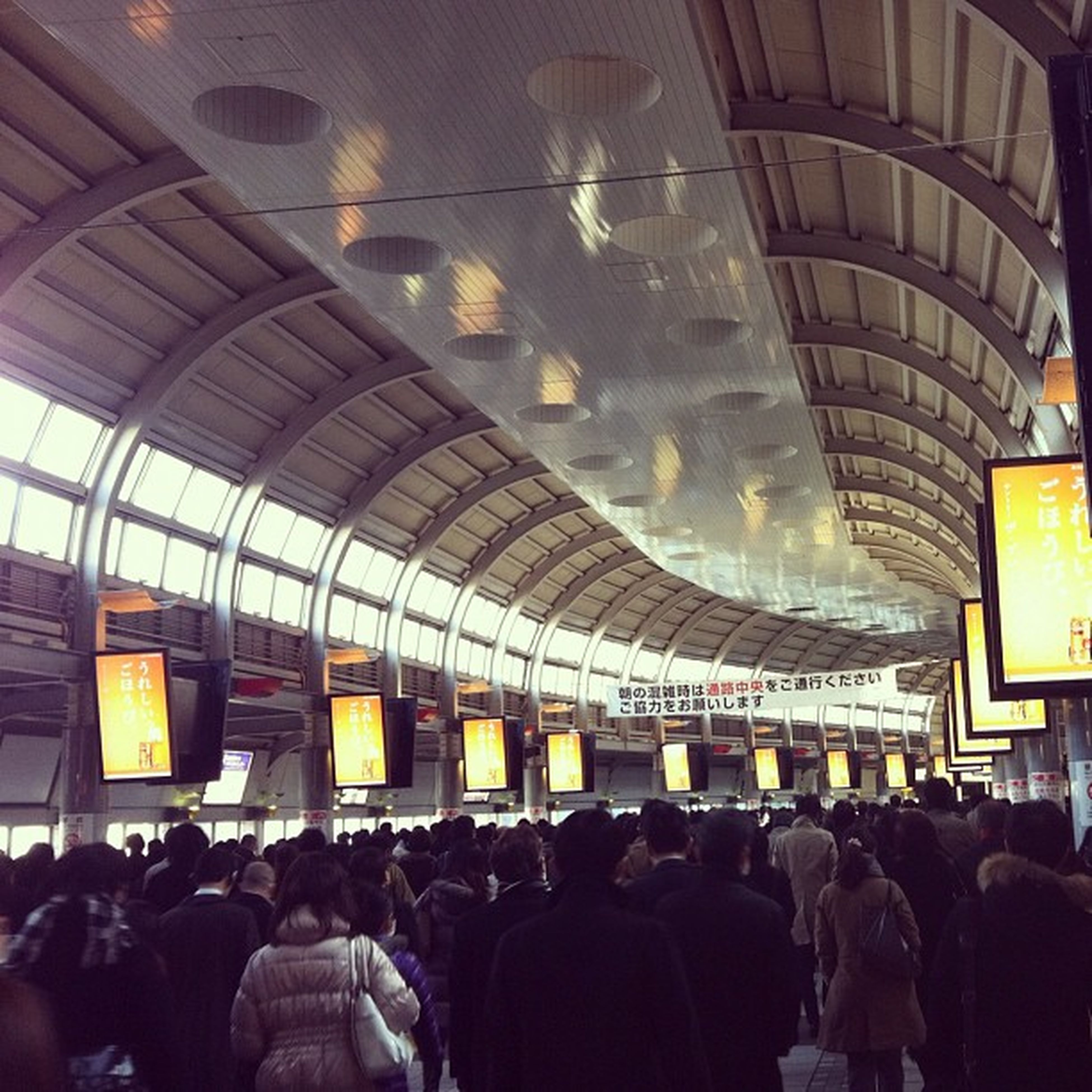 indoors, large group of people, public transportation, railroad station, men, transportation, illuminated, person, rail transportation, journey, passenger, crowd, lifestyles, travel, airport, ceiling, train - vehicle, in a row, subway station