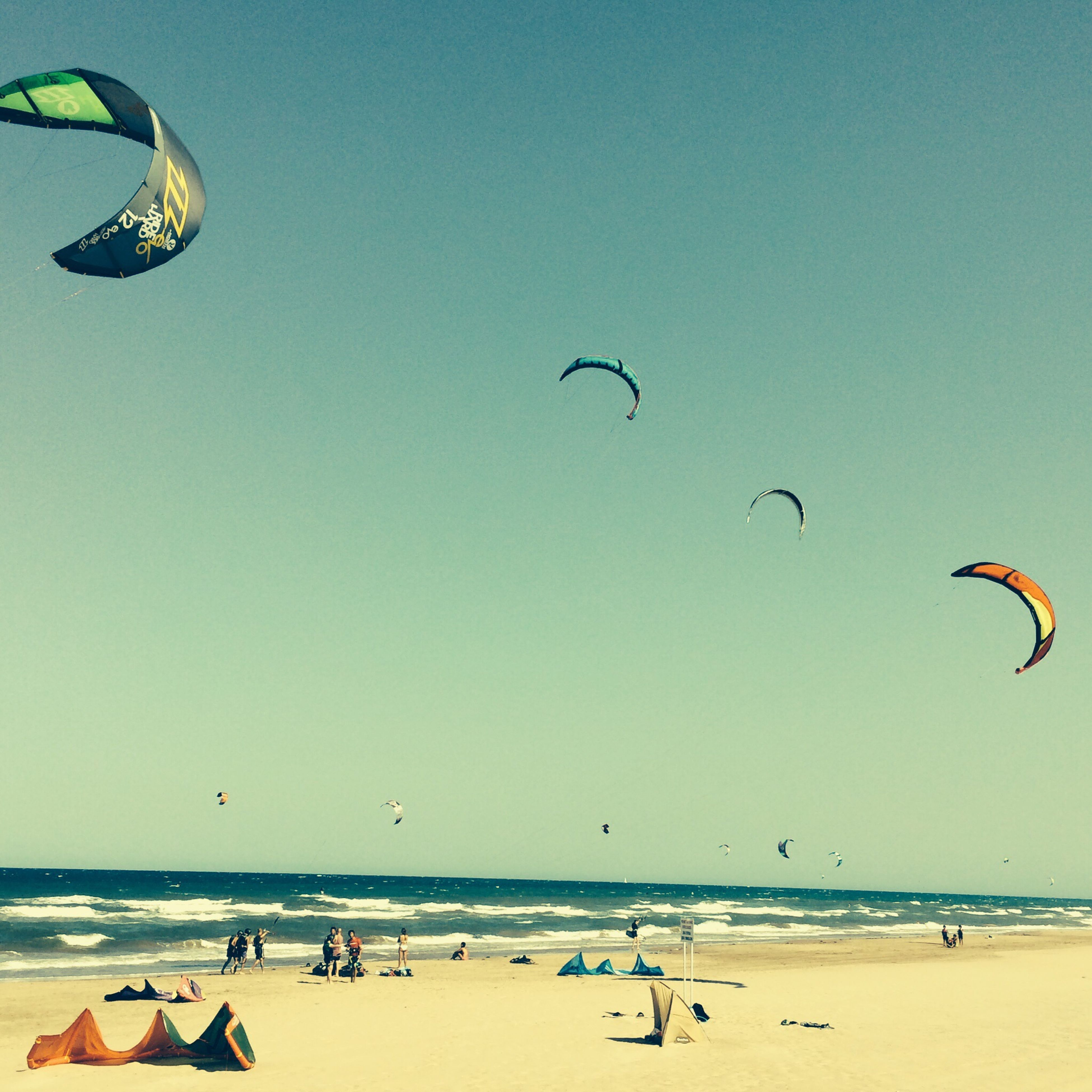 beach, sea, flying, sand, horizon over water, mid-air, vacations, leisure activity, parachute, water, shore, clear sky, enjoyment, large group of people, fun, blue, copy space, lifestyles, scenics