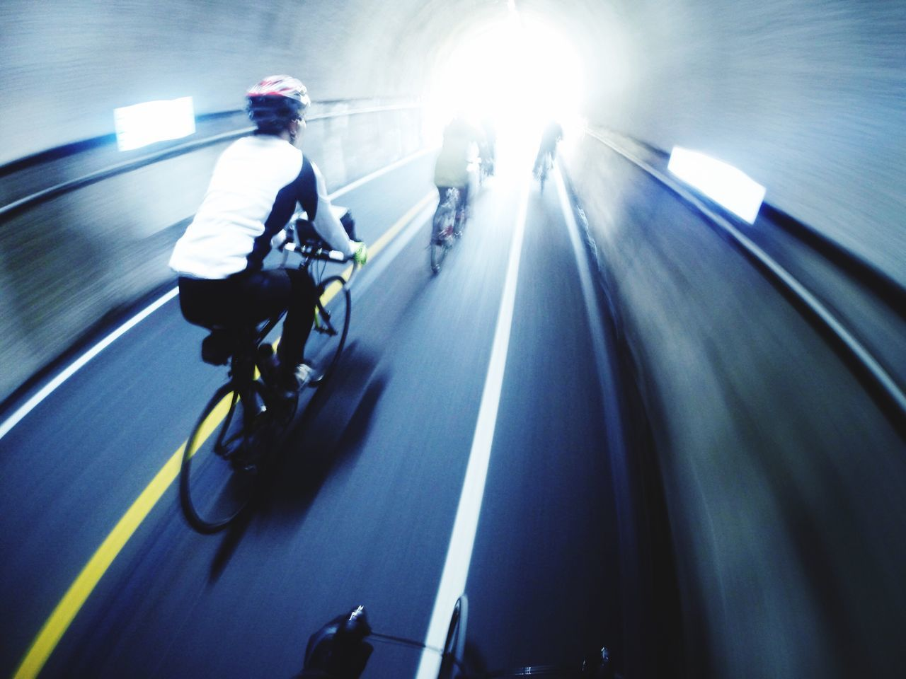People Riding Bicycle In Tunnel