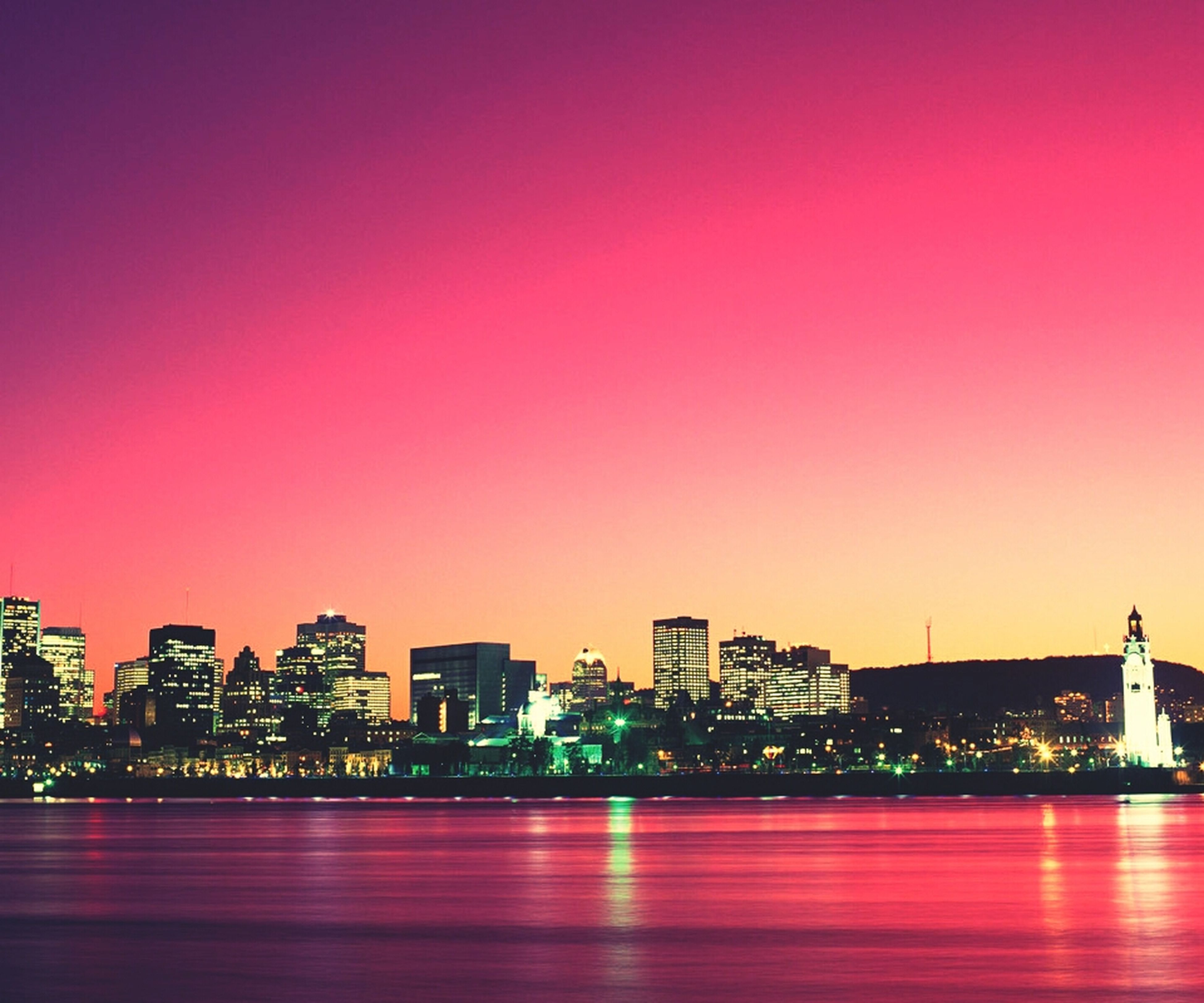 illuminated, architecture, city, building exterior, night, copy space, built structure, waterfront, clear sky, cityscape, orange color, water, red, sunset, sea, multi colored, modern, sky, skyscraper, urban skyline