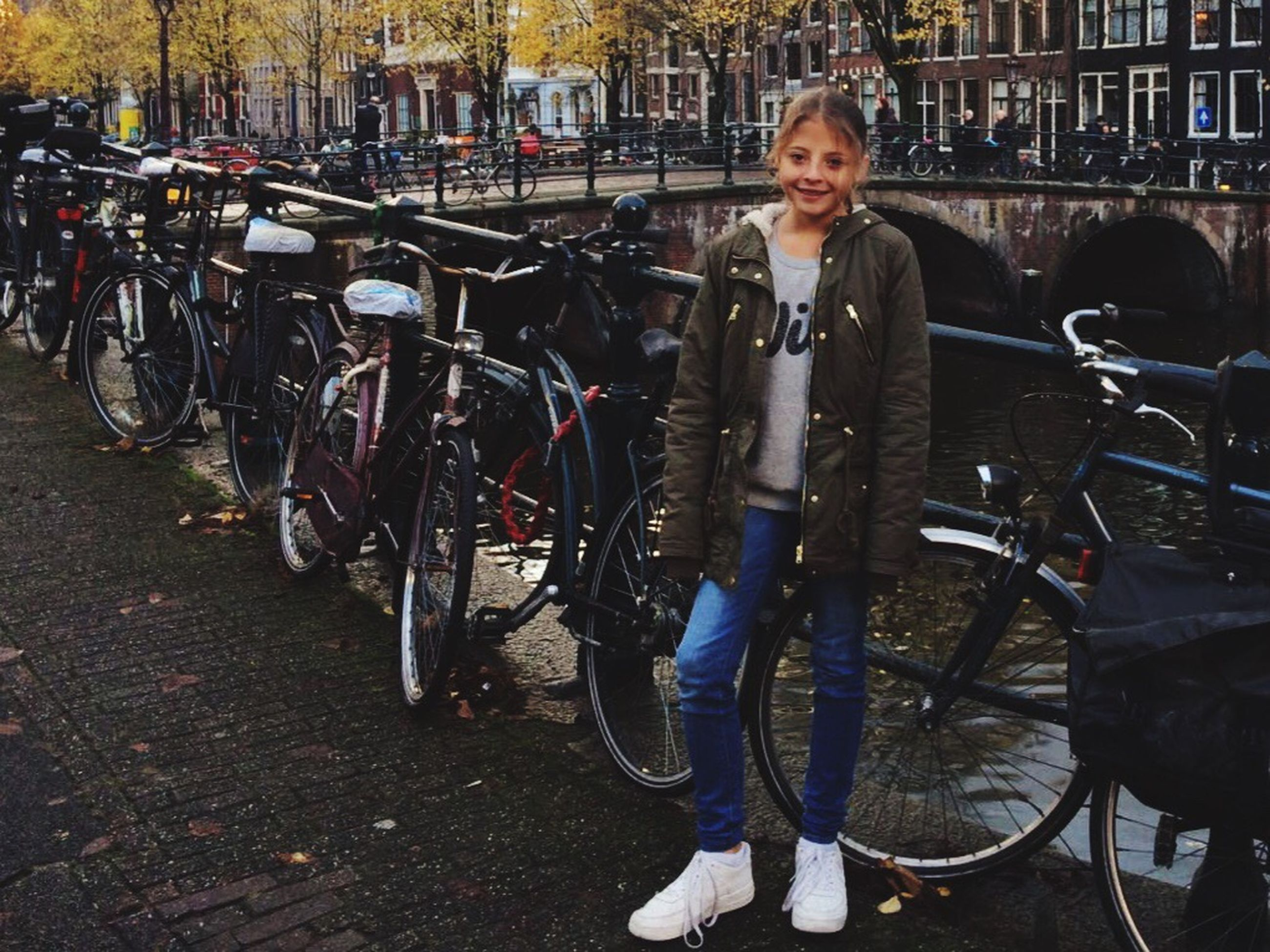 portrait, looking at camera, bicycle, city, casual clothing, transportation, adults only, mode of transport, lifestyles, one person, adult, people, outdoors, real people, one woman only, day