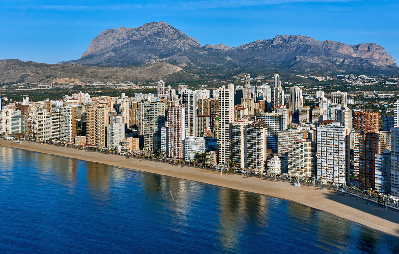 Aerial view of a Benidorm city coastline. Benidorm is a modern resort city, one of the most popular travel destinations in Spain. Costa Blanca, Alicante province Aerial View Alicante Province Spain Beach Beauty In Nature Benidorm City Cityscape Coast Coastline Day Highrise Architecture Landscape Mediterranean Sea Modern Architecture Mountains Picturesque Reflection Seaside Shoreline Skyscrapers SPAIN Sunny Day Tourist Resort TOWNSCAPE Travel Destinations