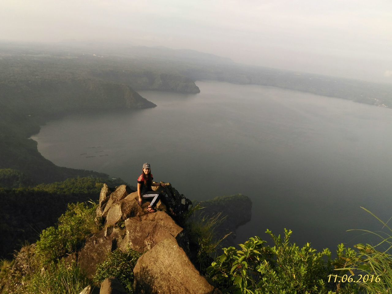 nature, real people, scenics, beauty in nature, mountain, two people, full length, outdoors, rock - object, high angle view, leisure activity, water, men, tranquility, lifestyles, day, fog, togetherness, sitting, sea, cliff, landscape, sky, young adult, people