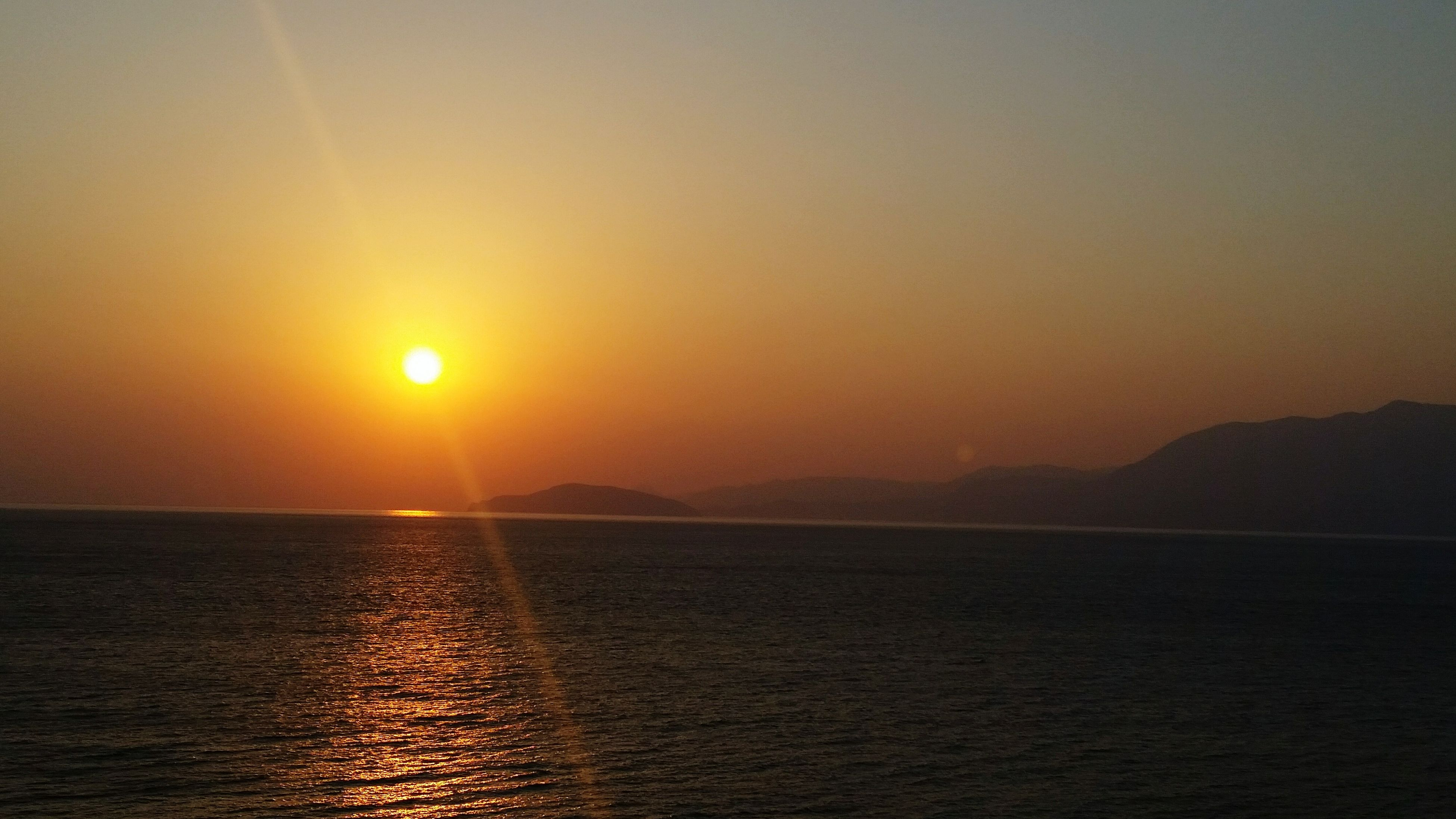 sunset, sun, water, sea, scenics, tranquil scene, tranquility, beauty in nature, waterfront, horizon over water, idyllic, nature, reflection, orange color, sunlight, sky, rippled, mountain, clear sky, silhouette