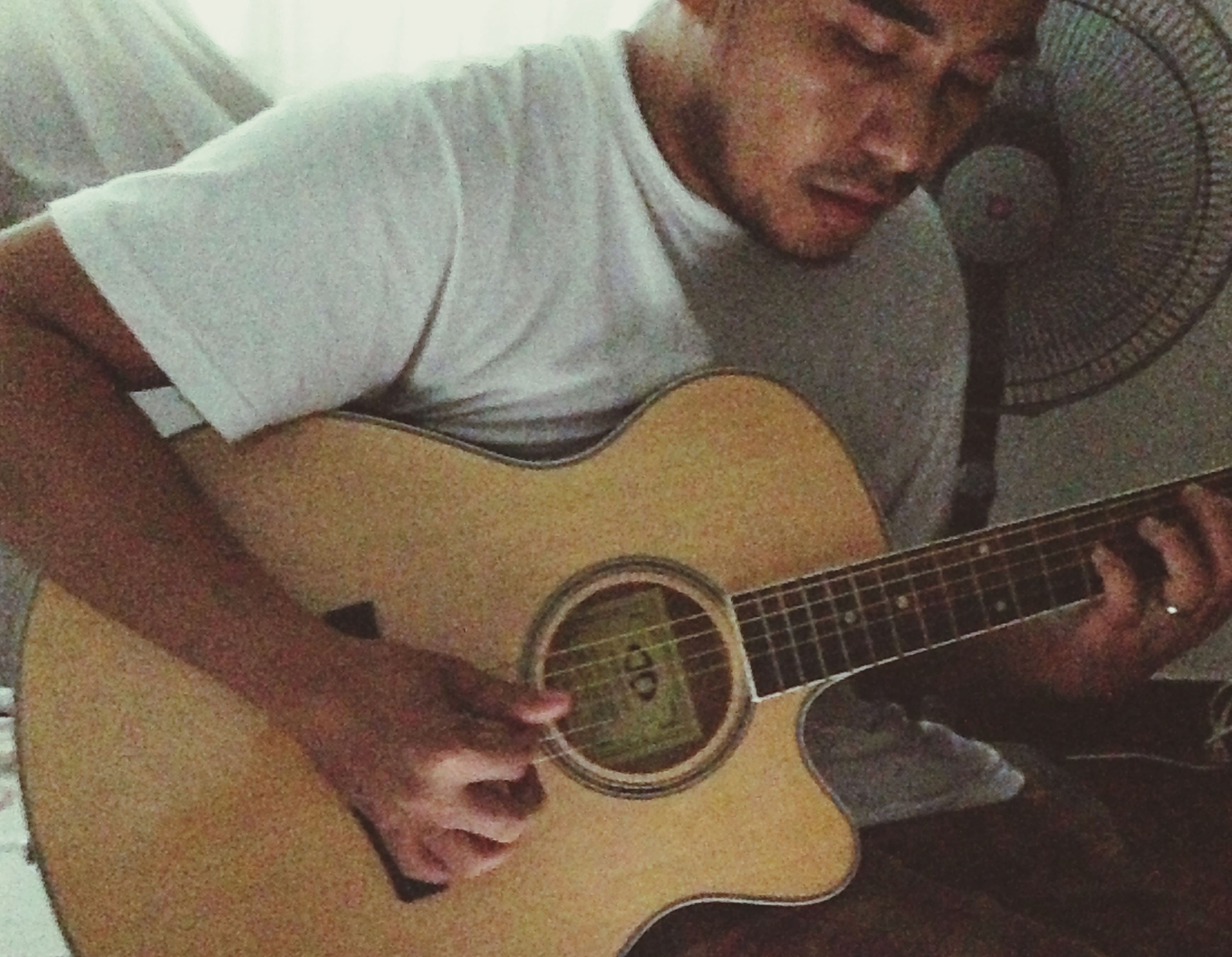 indoors, music, lifestyles, musical instrument, holding, guitar, arts culture and entertainment, leisure activity, casual clothing, person, sitting, technology, wireless technology, musical equipment, young adult, home interior, playing