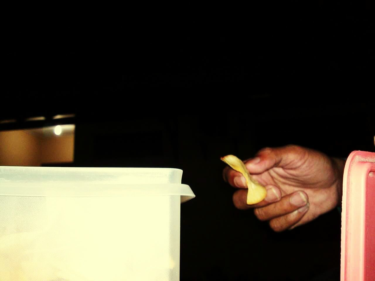 human hand, human finger, human body part, real people, indoors, one person, black background, food, close-up, people