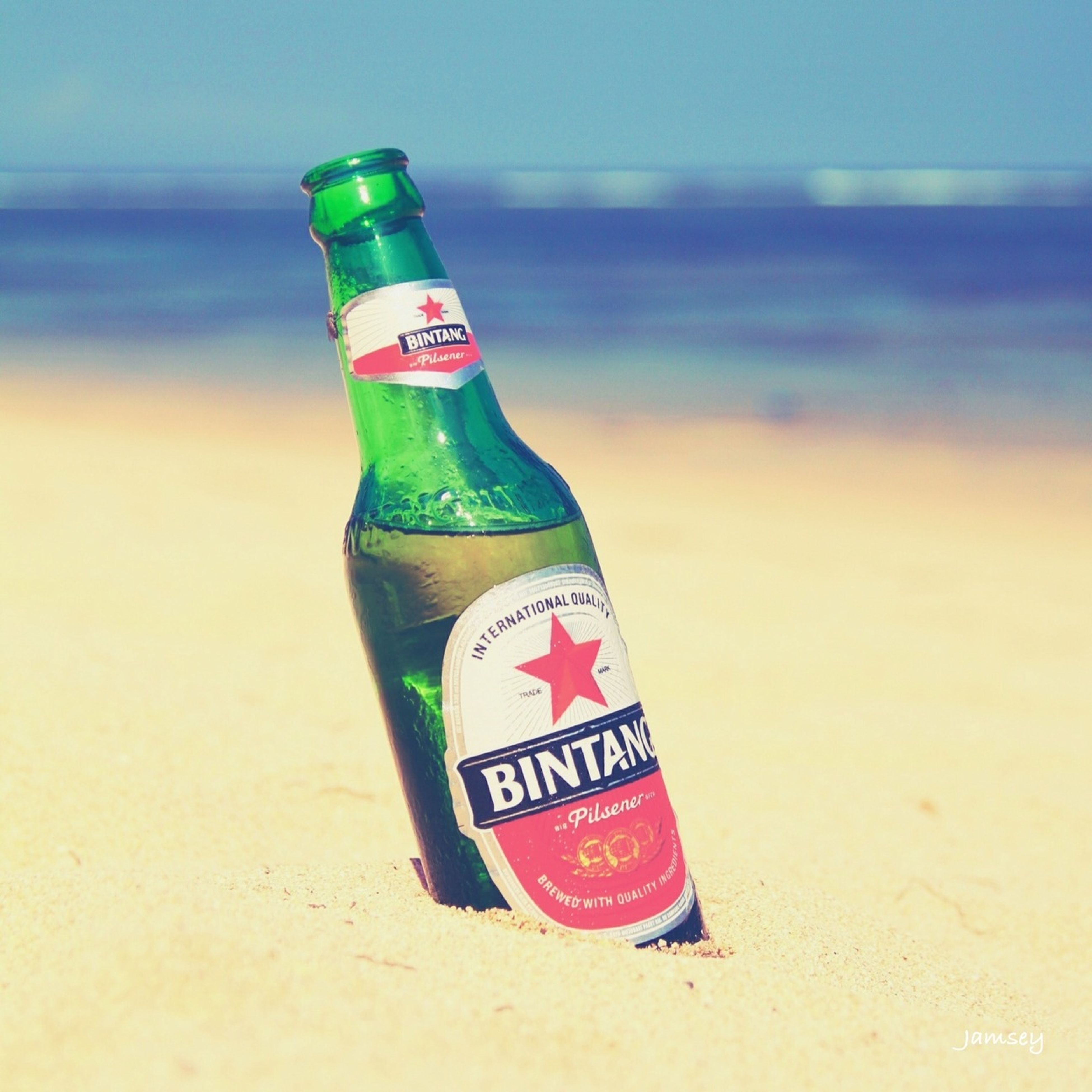 text, western script, communication, close-up, beach, red, focus on foreground, sea, still life, guidance, no people, sand, capital letter, shore, selective focus, day, water, outdoors, bottle, horizon over water