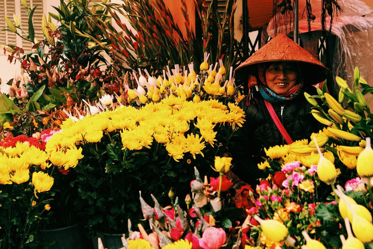 flower, yellow, growth, real people, beauty in nature, fragility, smiling, nature, outdoors, day, freshness, plant, happiness, bouquet, looking at camera, flower market, portrait, flower head, one person, people
