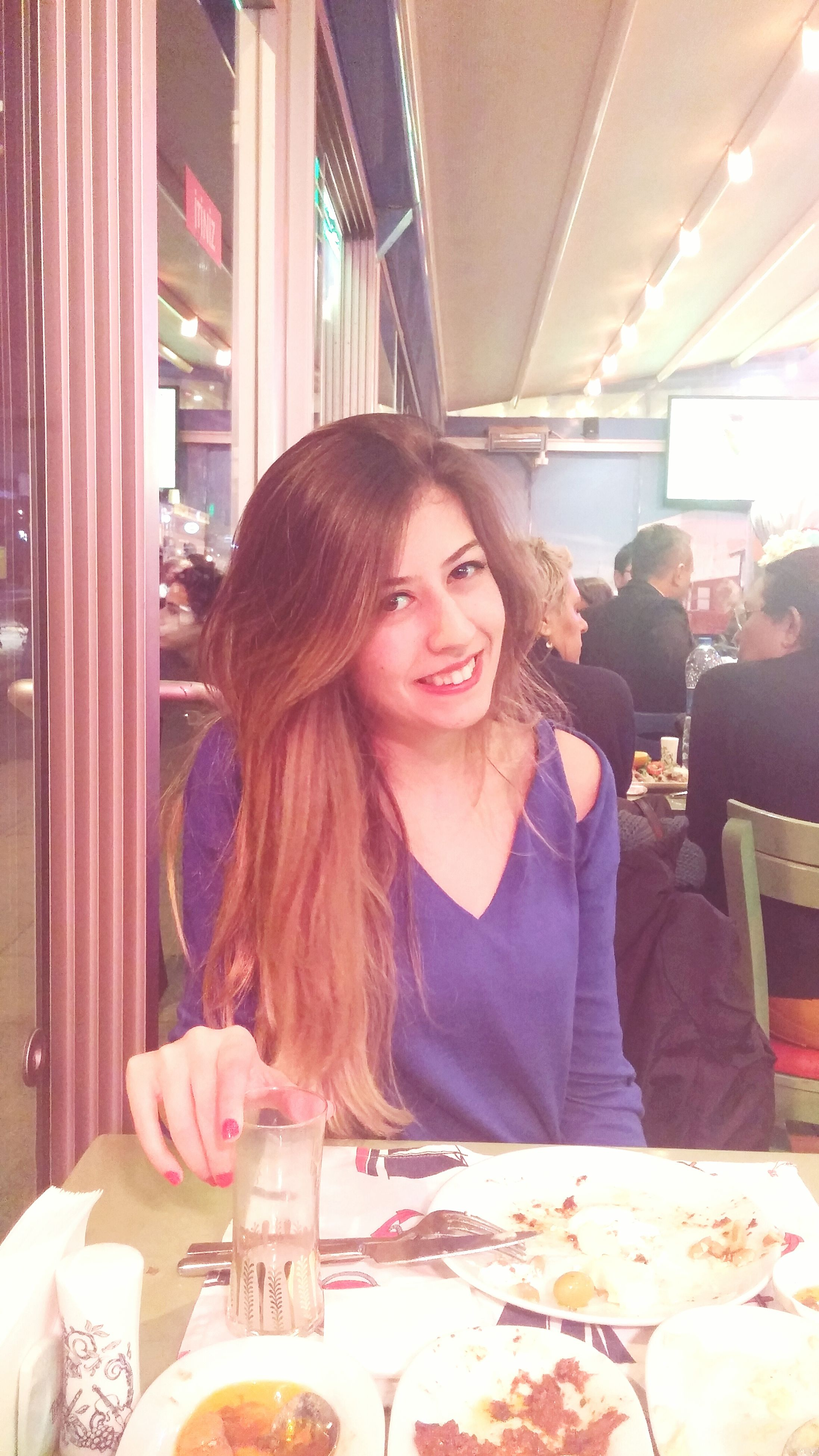 indoors, young adult, lifestyles, person, young women, leisure activity, sitting, casual clothing, waist up, portrait, looking at camera, headshot, front view, smiling, food and drink, wireless technology, long hair, restaurant