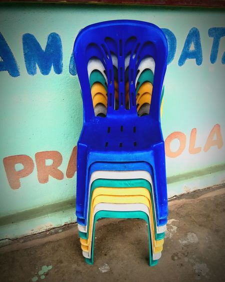 Chairs Outdoors Multi Colored Street Art Close-up Chairs Outdoors Colourful Chairs Chairs Seats Chairs Outside Blue Chairs Yelow Chairs Colourful Colours Of Life Colours And Patterns Blue Architecture Text Graffiti No People Day