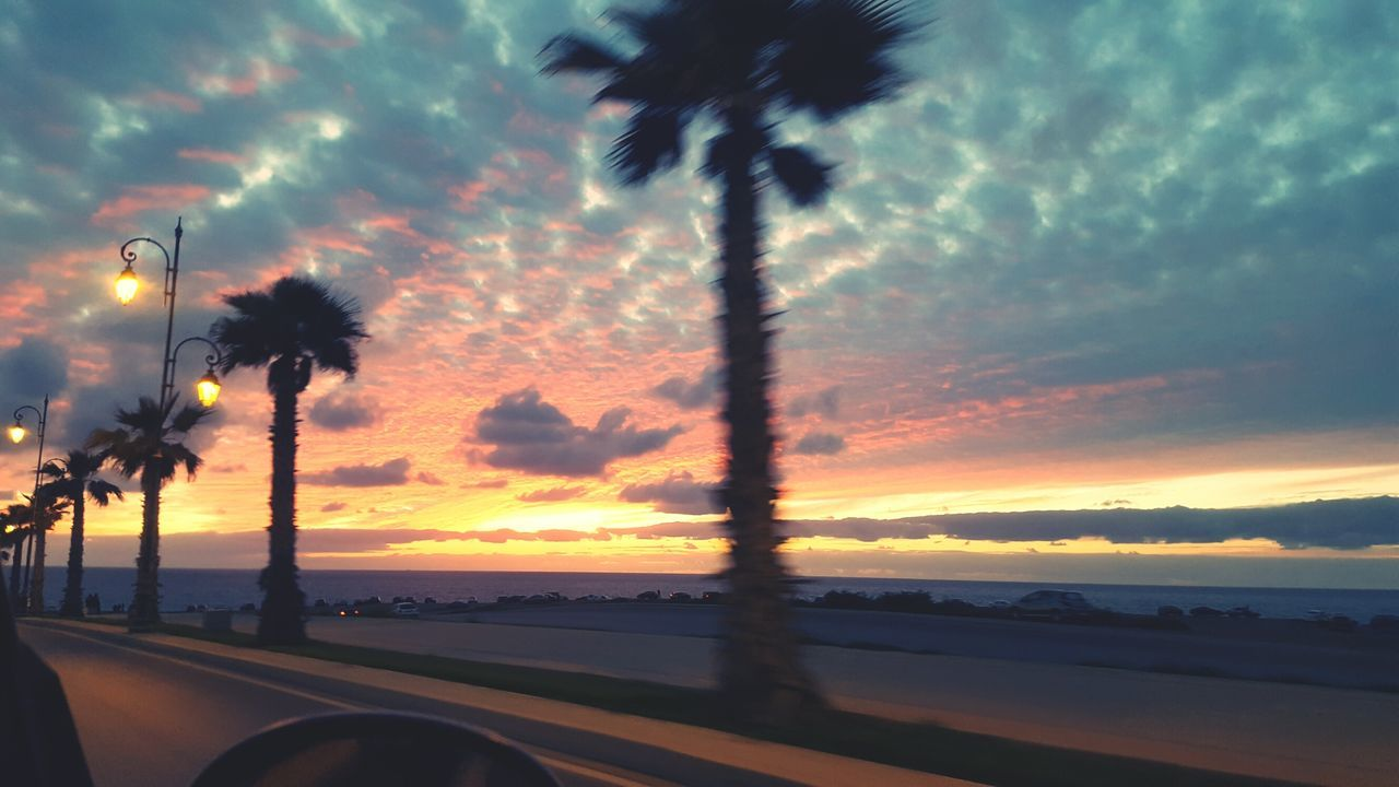 sunset, sky, cloud - sky, dramatic sky, beauty in nature, silhouette, tree, scenics, nature, no people, street light, outdoors, palm tree, road, sea, water, day