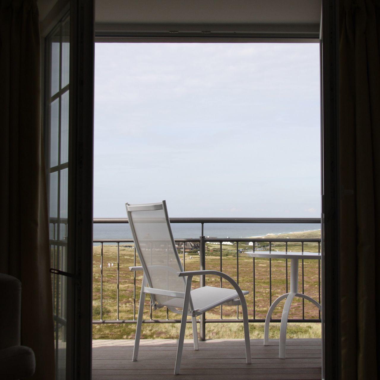 Armchair And Table In Balcony Seen Through Doorway