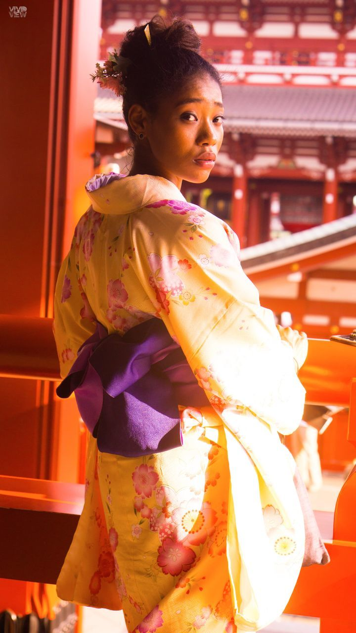 traditional clothing, real people, religion, celebration, cultures, standing, lifestyles, mid adult women, one person, young adult, young women, tradition, side view, happiness, spirituality, sari, smiling, built structure, architecture, kimono, beautiful woman, outdoors, day