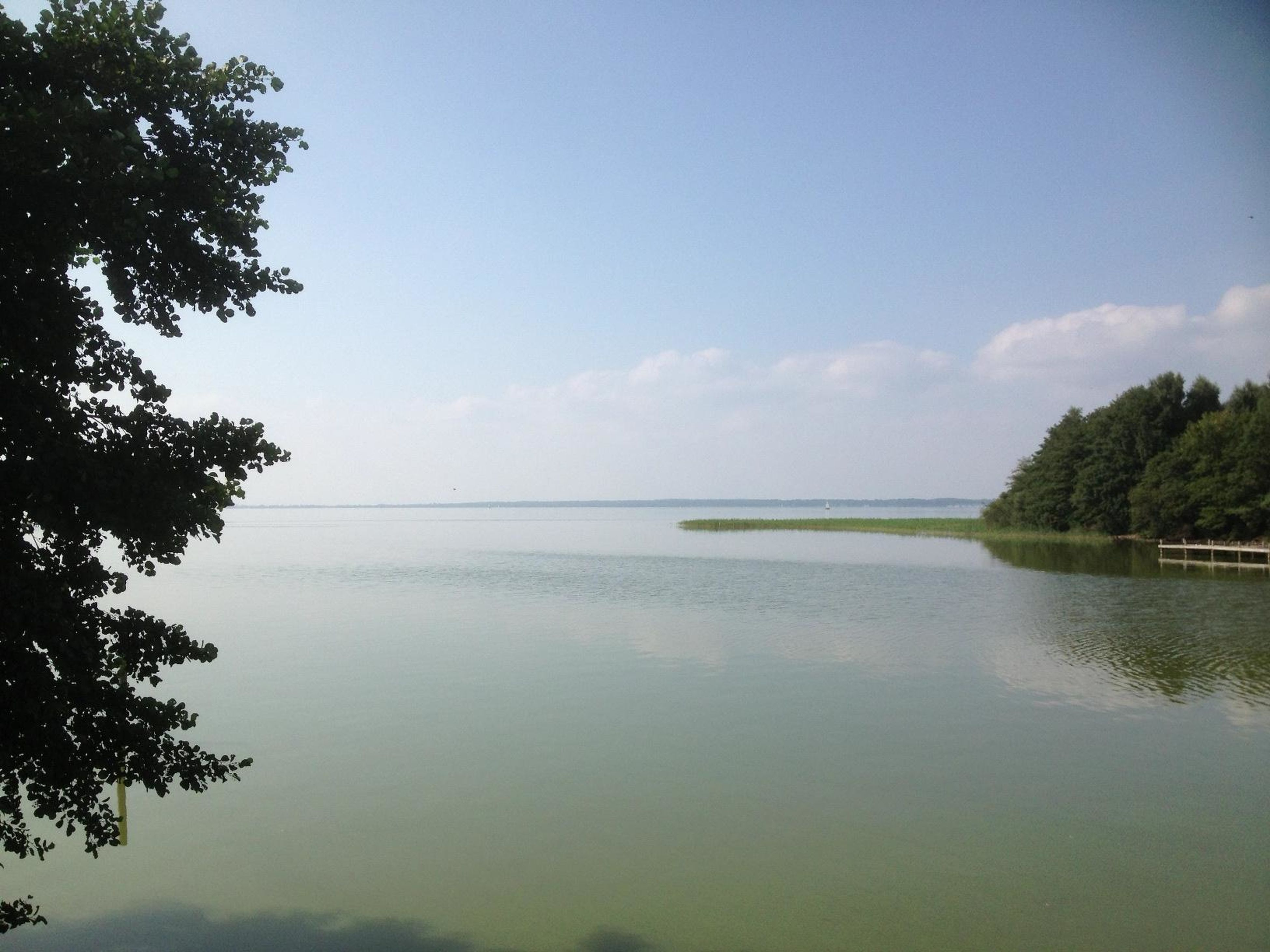 water, tranquil scene, tranquility, scenics, tree, beauty in nature, sky, waterfront, reflection, nature, lake, sea, horizon over water, idyllic, calm, rippled, outdoors, no people, cloud, day